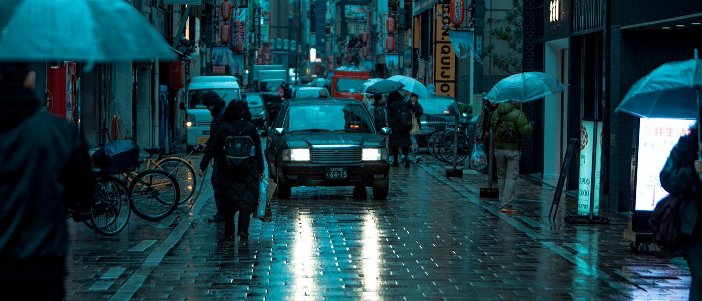 Image may contain: umbrella, rain and building