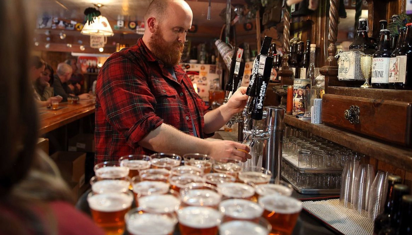 A brew master tapping up lots of beer on a tray in a bar. He's wearing a checkered red shirt.