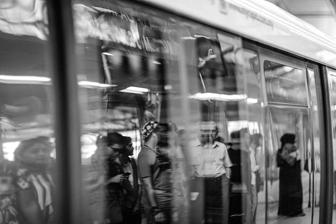 People's images reflected in a train on a platform in Kuala Lumpur, Malaysia.