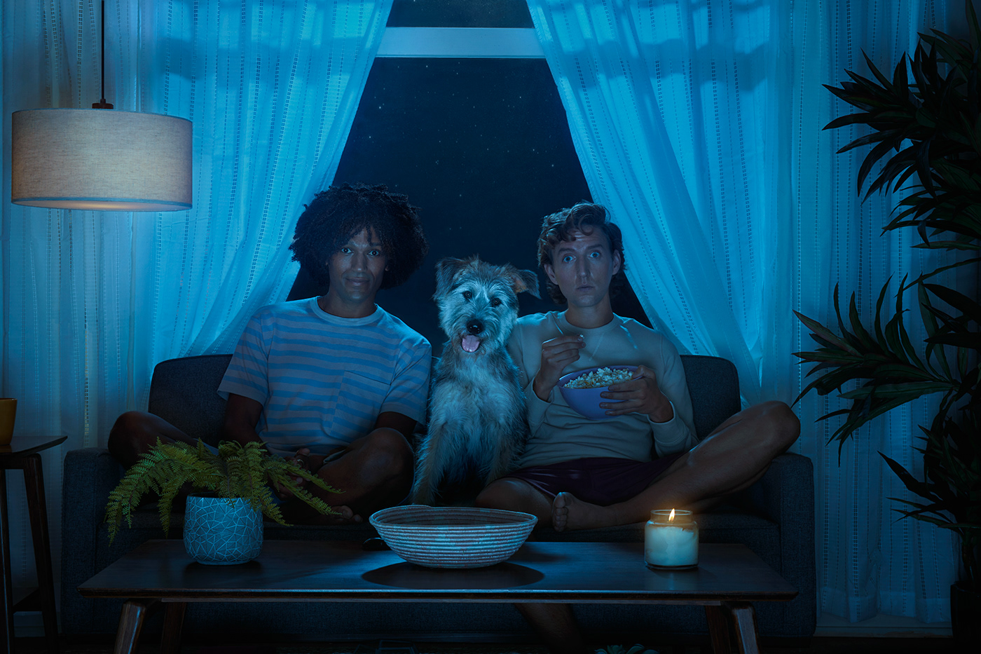 two men and their dog watch TV in the dark.