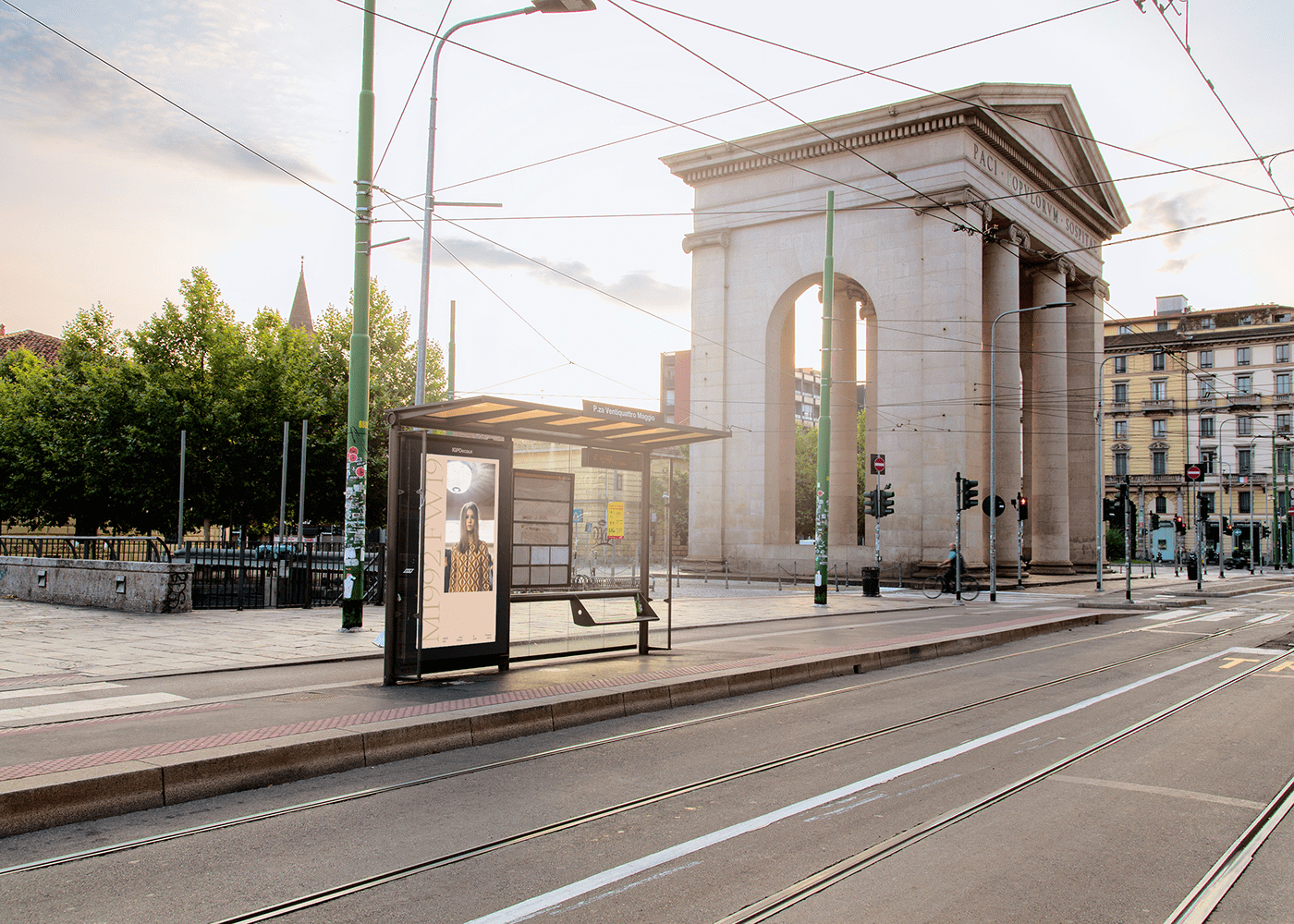 Photo of a bus stop in Milan with one of the posters made by me