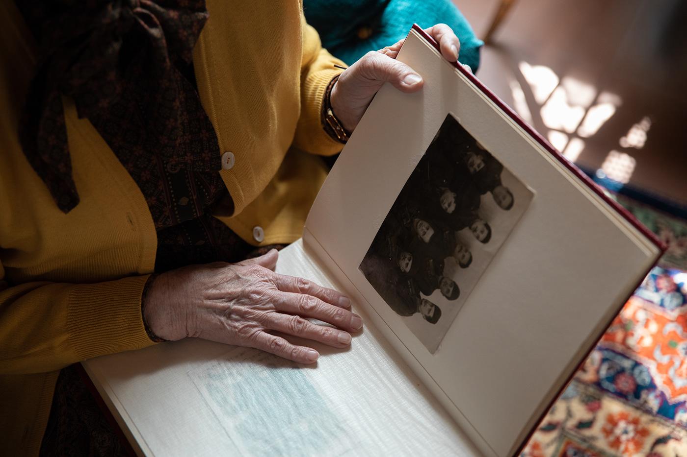 old woman grandmother house living room vintage book hands storytelling   War