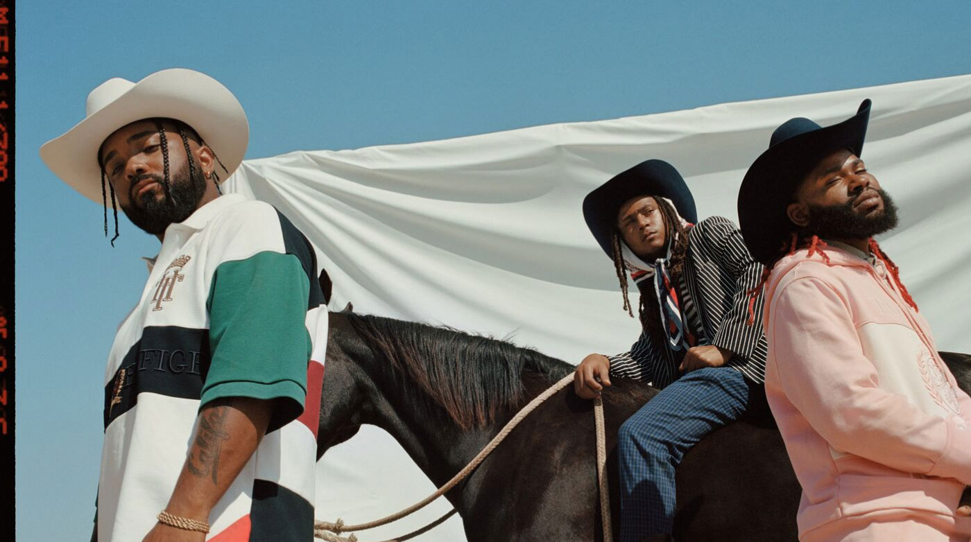 The Compton Cowboys wearing Tommy Hilfiger clothing, cowboy hats, and riding a horse.