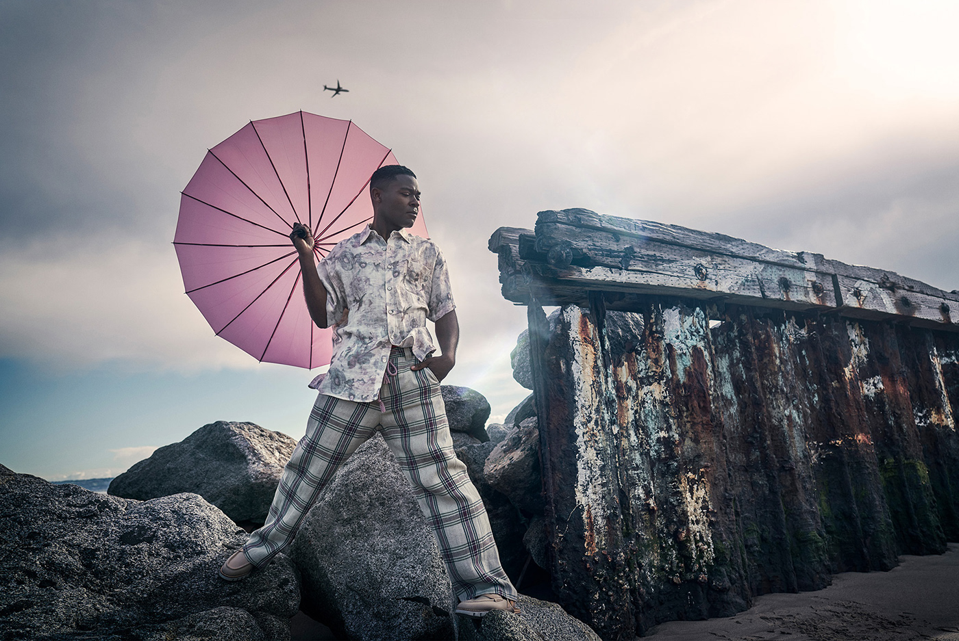 Celebrity David Oyelowo photographed with an pink umbrella at the sea for Alexa Magazine.