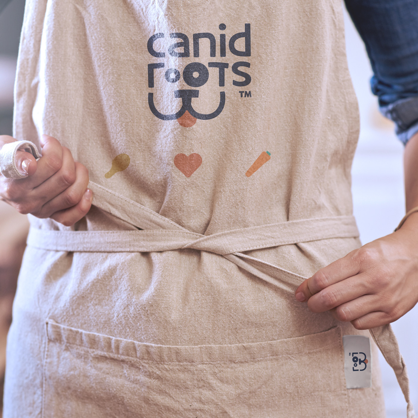 A cook is seen tying his apron. The Canid Roots logo is printed on it. He appears to be in a kitchen