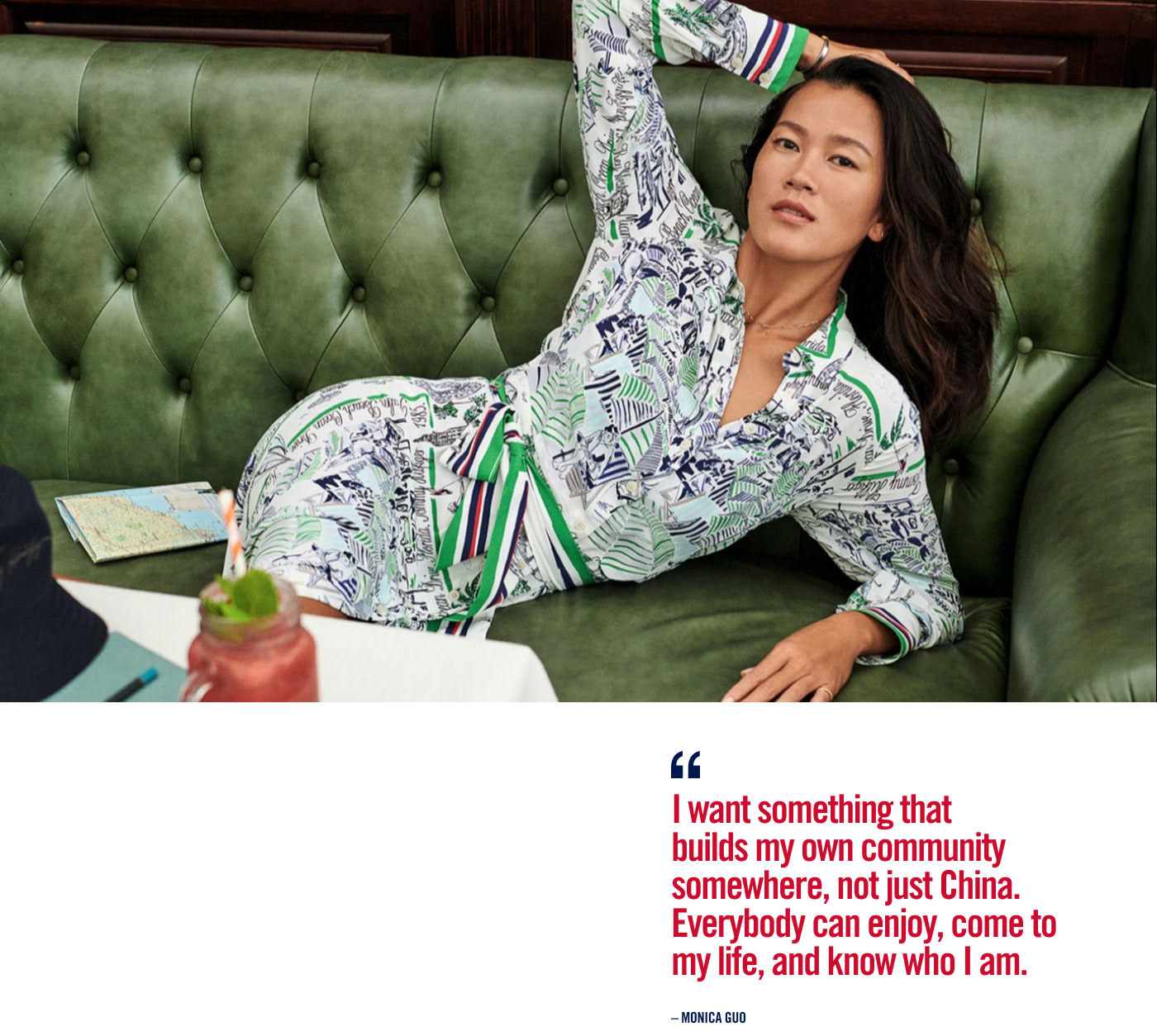 Monica Guo laying on a couch wearing a green crazy patterned dress