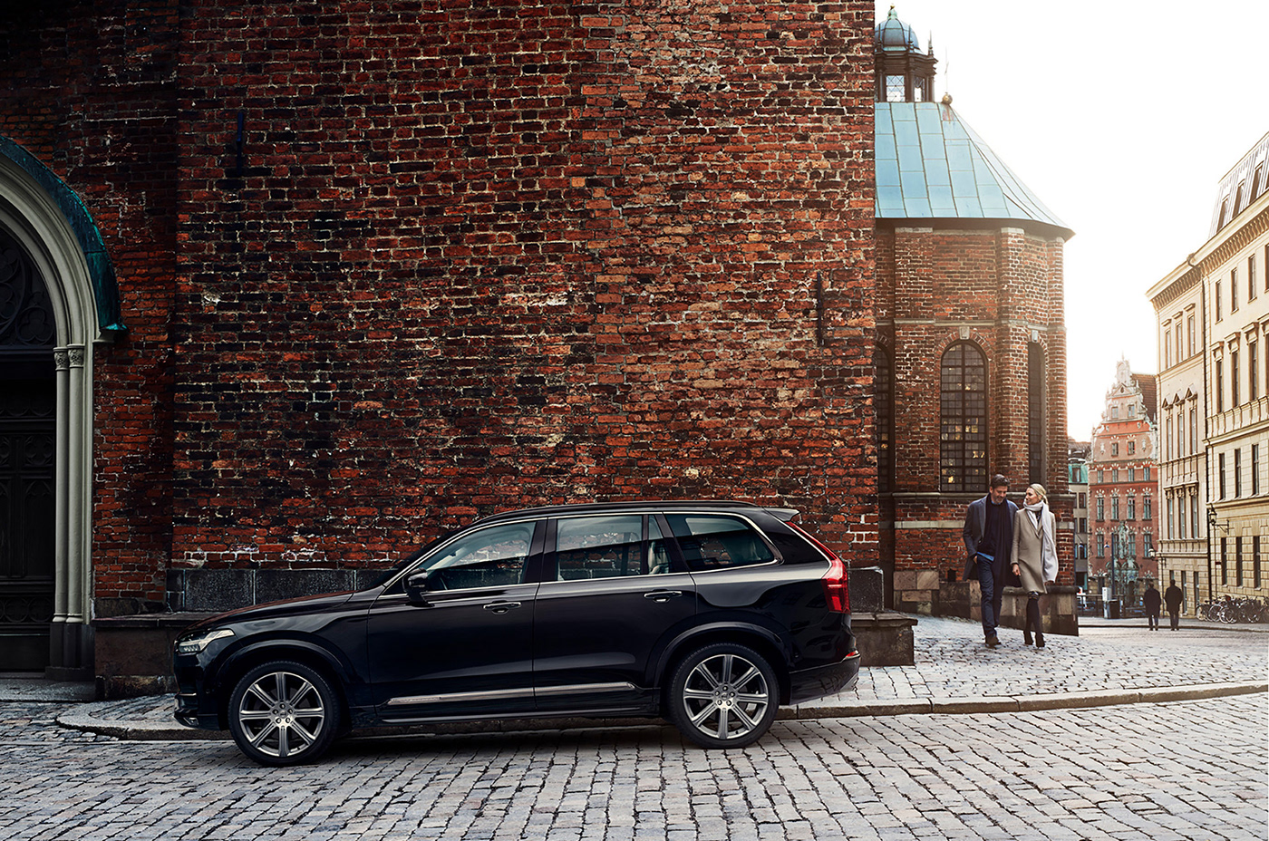 A black suv Volvo XC90 parking in front of a church with a couple walking by.