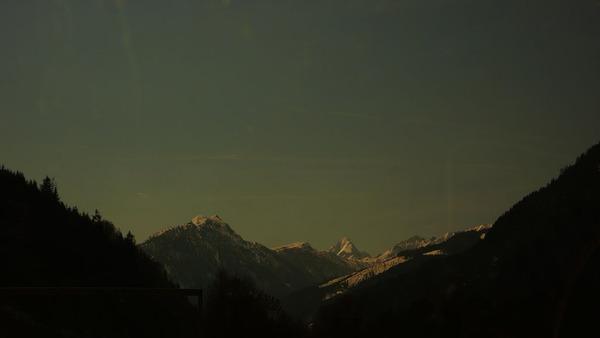 hills peak snow dark light trees alps Europe