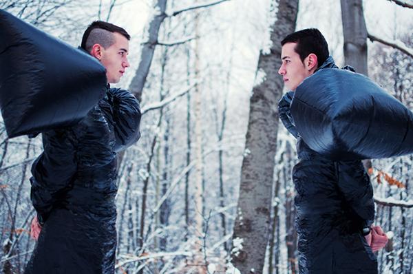 Confrontation male model body avant-garde black forest conceptual set mohawk shoot bag plastic art snow dof composition