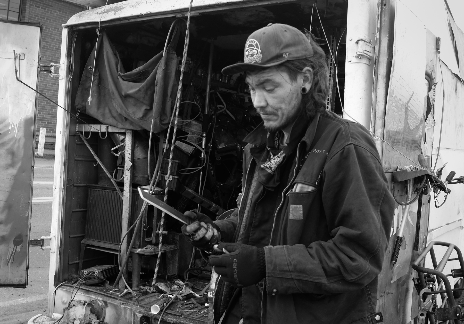 A man wearing a ball cap holding a long bladed knife behind a messy trailer