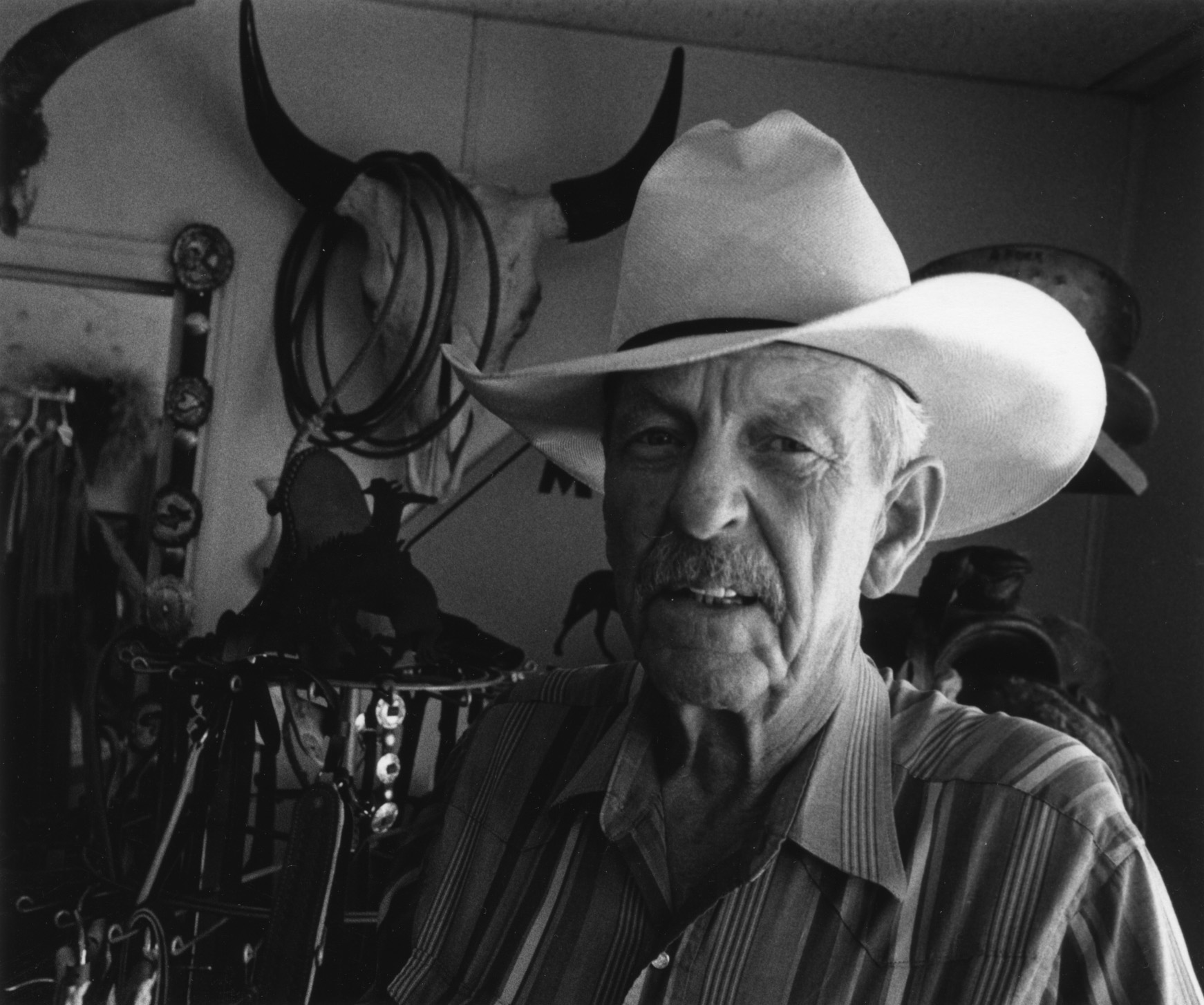 Man with a cowboy hat in a room with cowboy paraphernalia