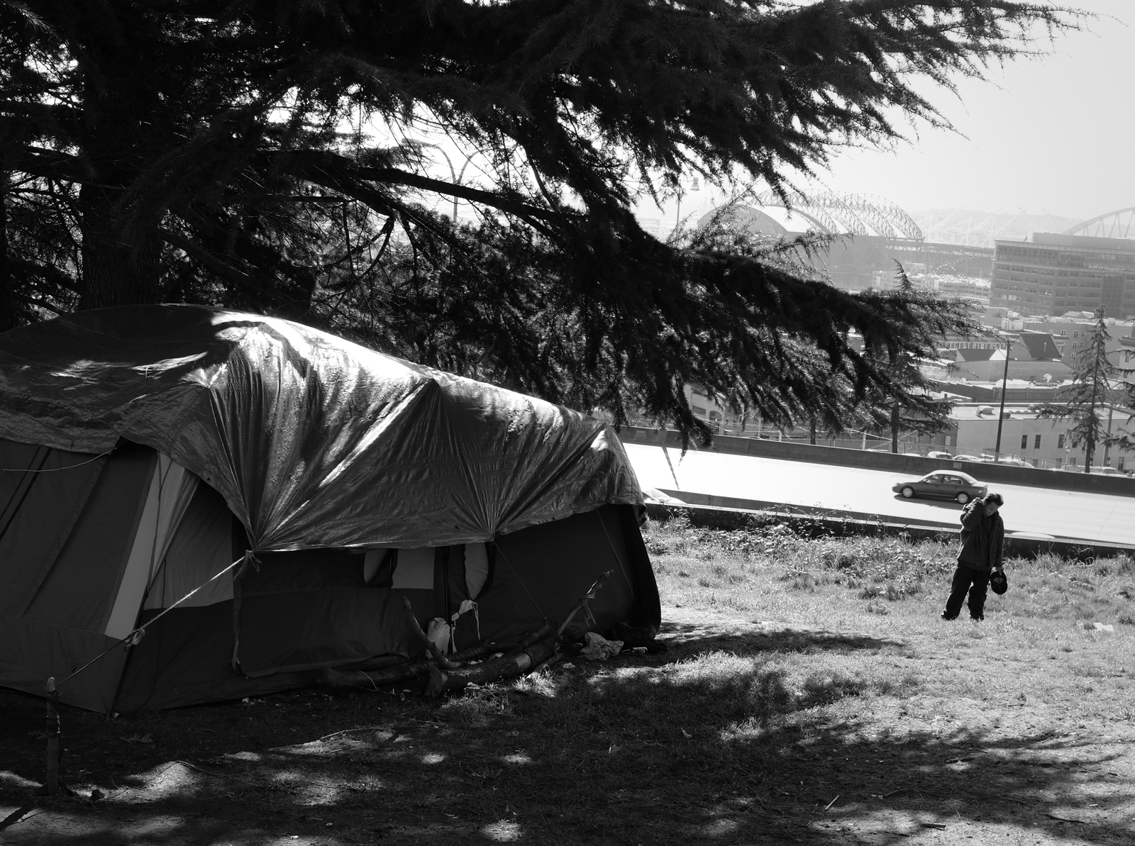 A man walks up a hillside with a tent in the foreground and the Seattle city skline in the back