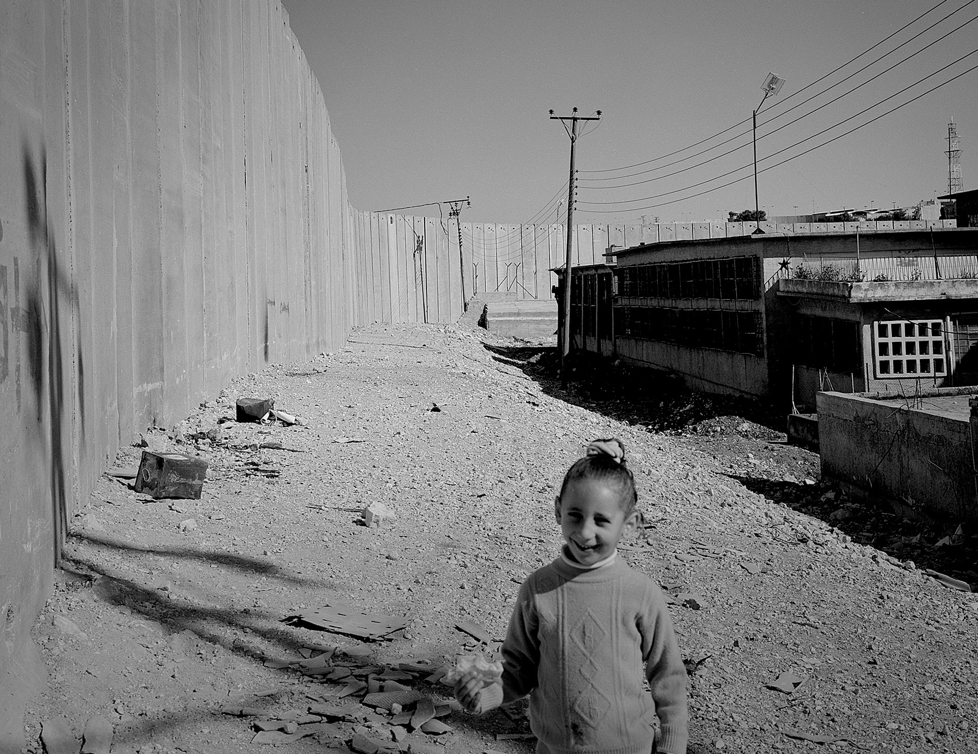 A young girl looks at the viewer with a high concrete wall stretching out behind her