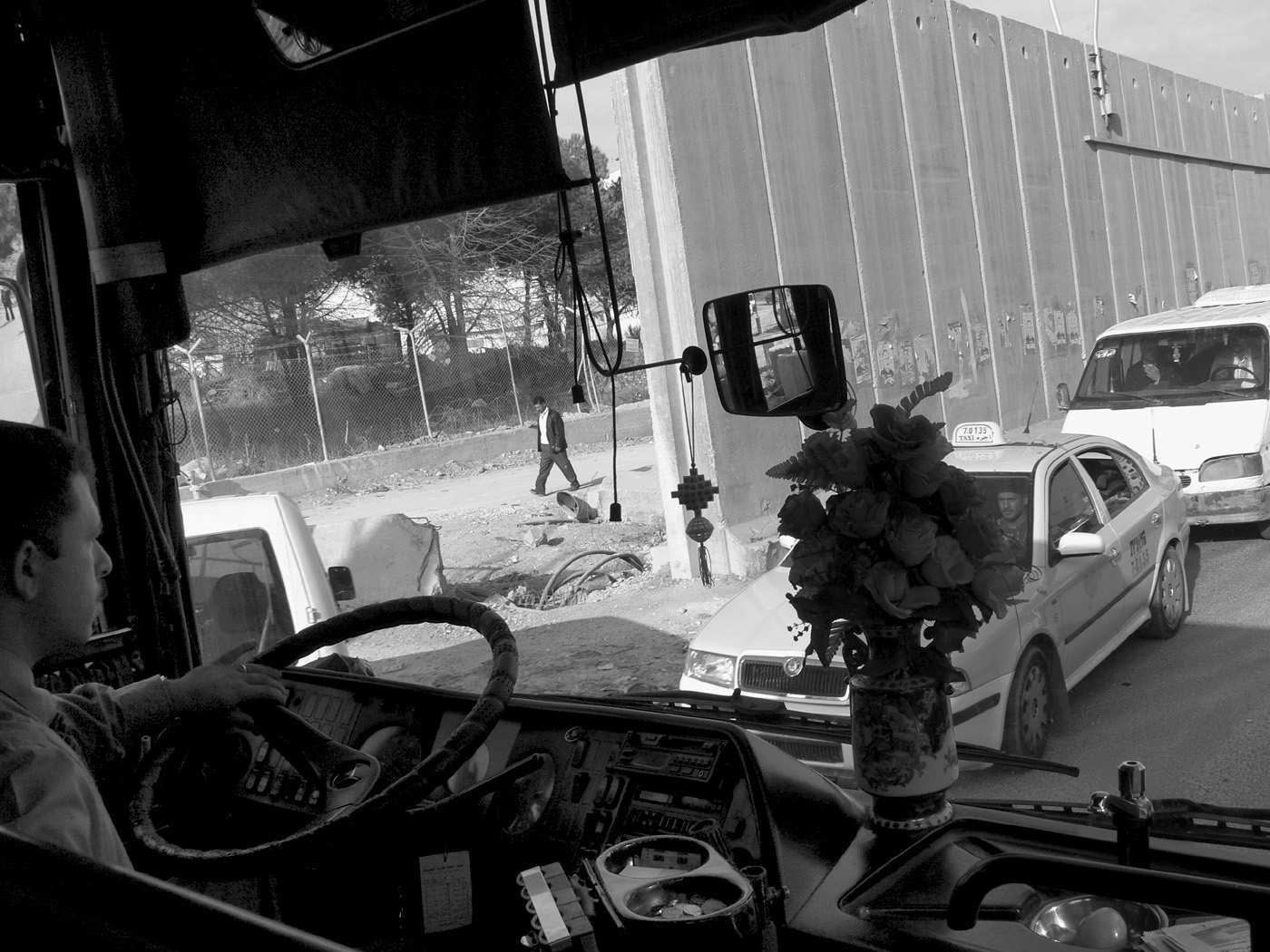 A view of a concrete wall and traffic from a bus windshield