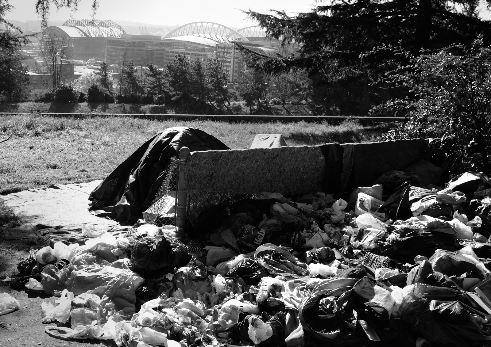 A pile of garbage in the foreground with a tent and the city skyline in the back