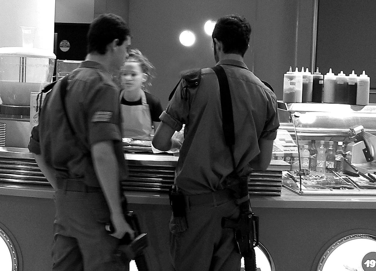 Two young israeli soldiers with assault rifles slung at their sides buy food at a deli
