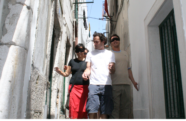 A guide leads blindfolded people down a narrow Lisbon street as part of sensorial lisbon, an innovative blindfolded tourism experience