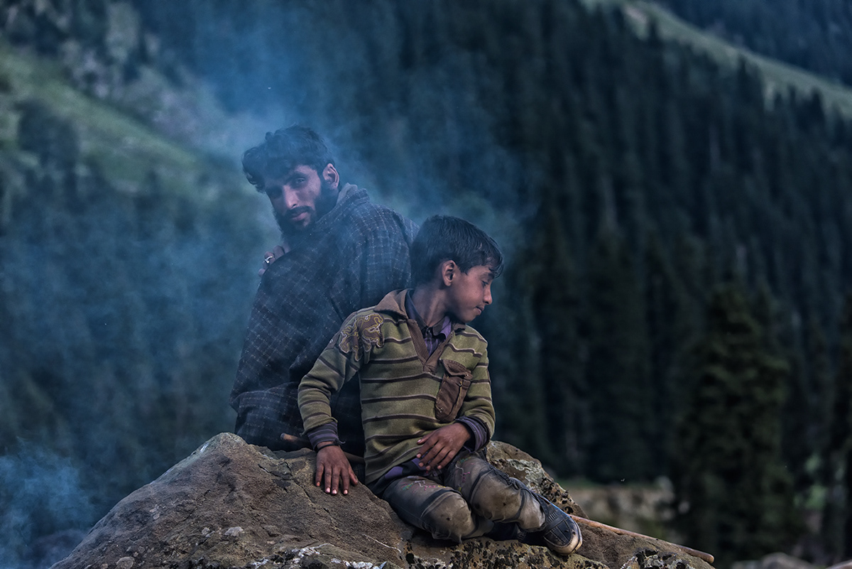 A father son duo warm themselves in the fire they have built to cook dinner
