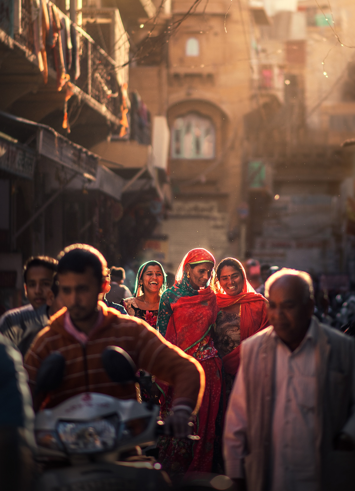 Three women smiling and passing in sunlit street in Jaisalmer India photography by Ashraful Arefin