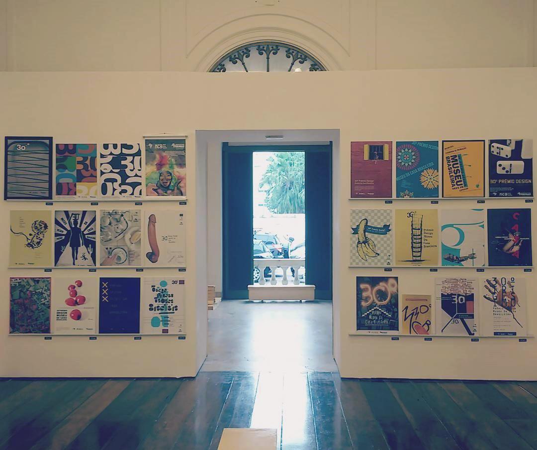 Foto de uma ambiente interno (parede - porta - parede). Nas duas paredes estão carregadas de cartazes pendurados.