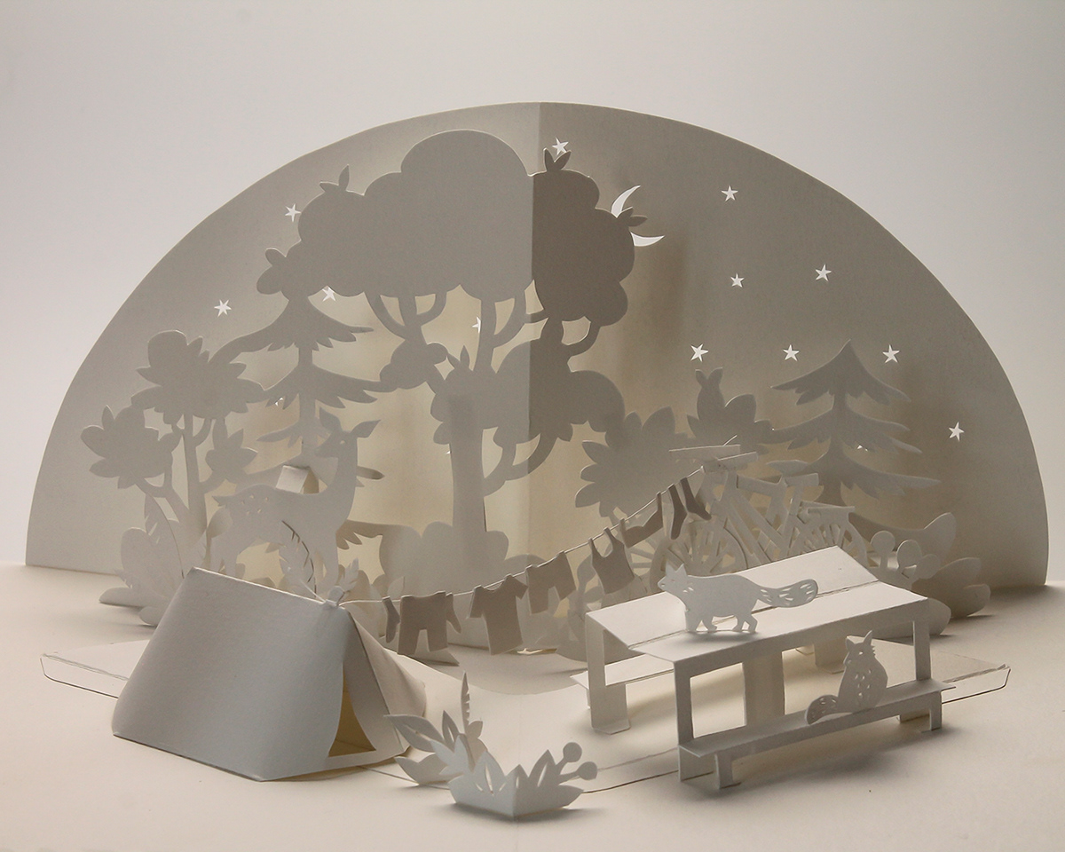 monochrome white pop-up scenery of a campground scene with trees, a tent, bikes and a picnc table