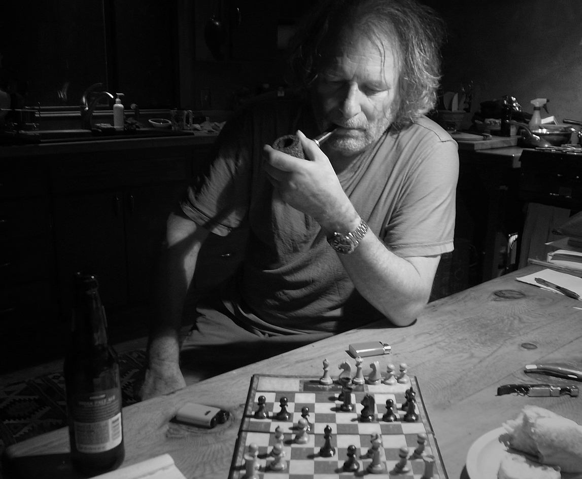 Man smoking a pipe and staring at a chess game