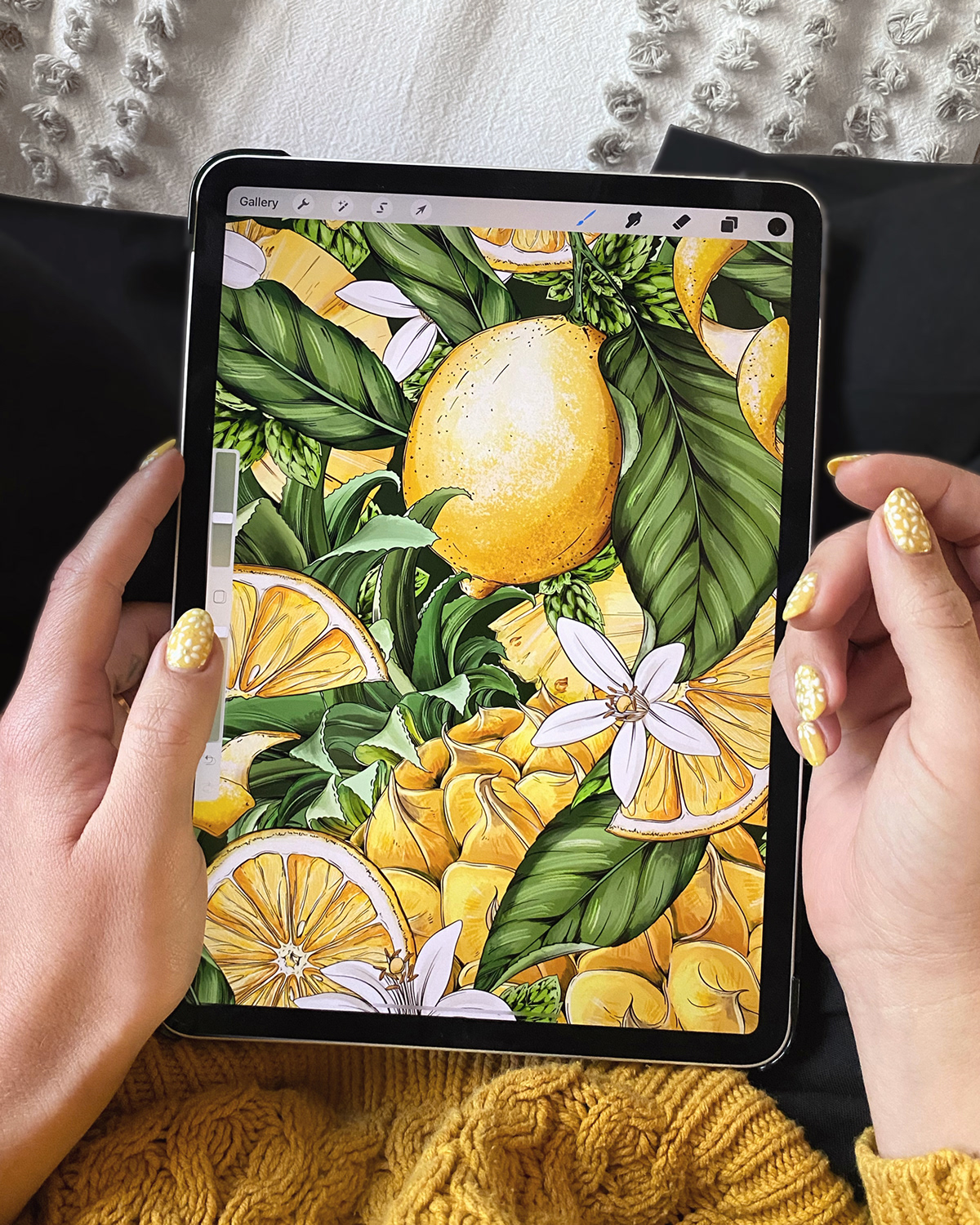 top down photograph of hands holding an ipad pro displaying a citrius fruit illustration.