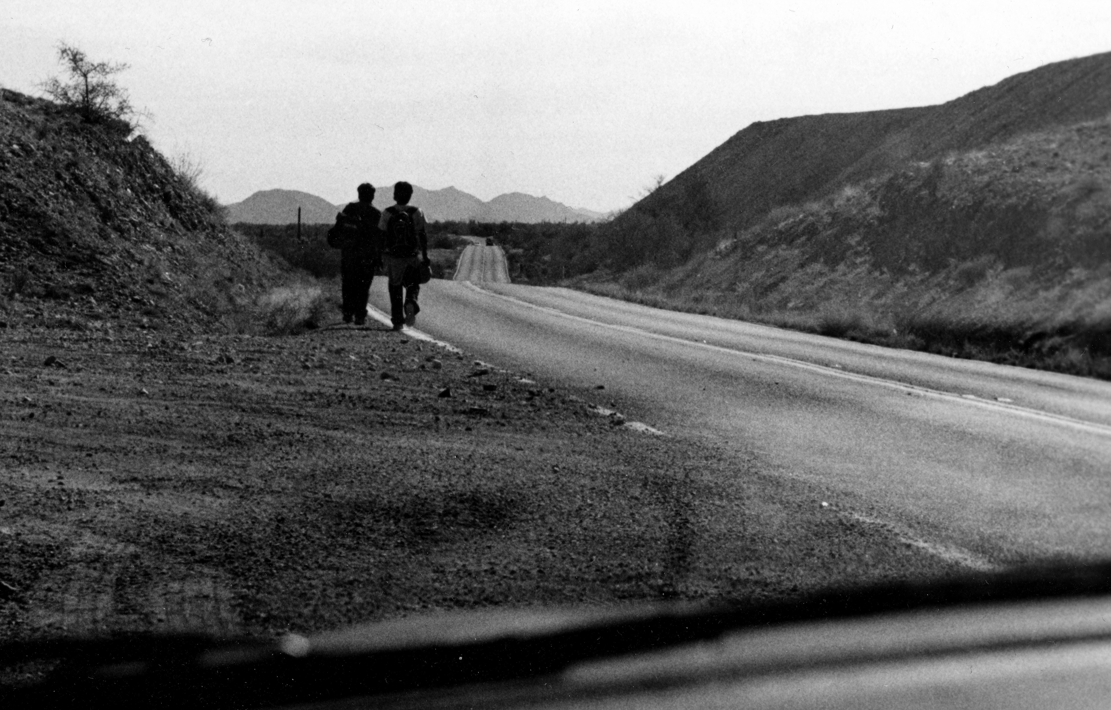 Two dark figures walk by the side of the road in a desert