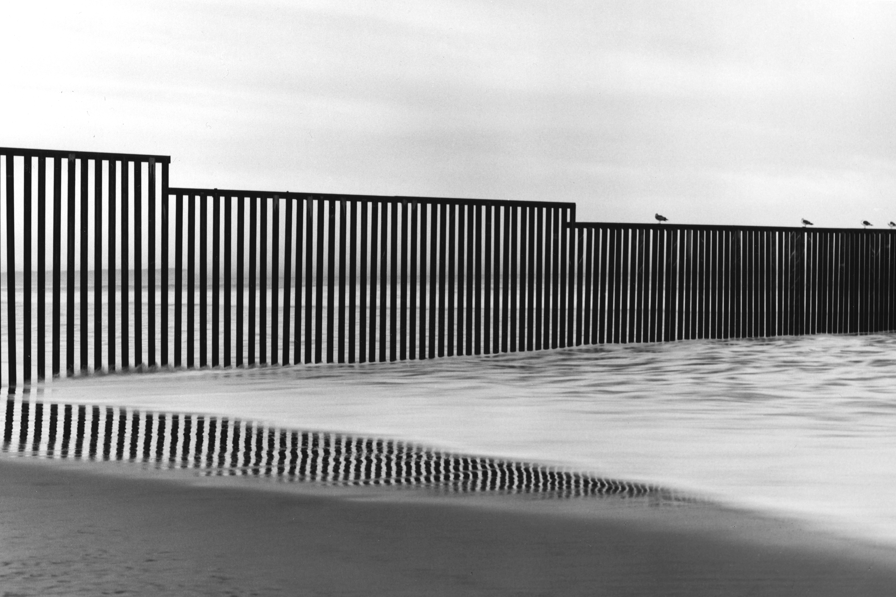 A barred fence stretches across the beach into the water