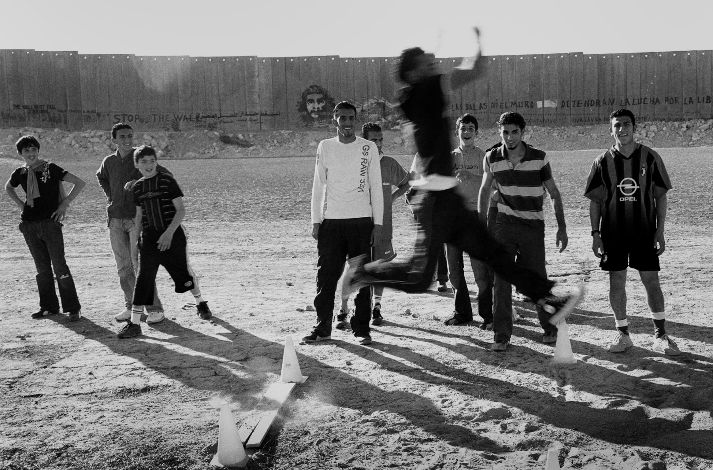 A group of youn men watch as another does a long jump in the dirt in front of a concrete wall