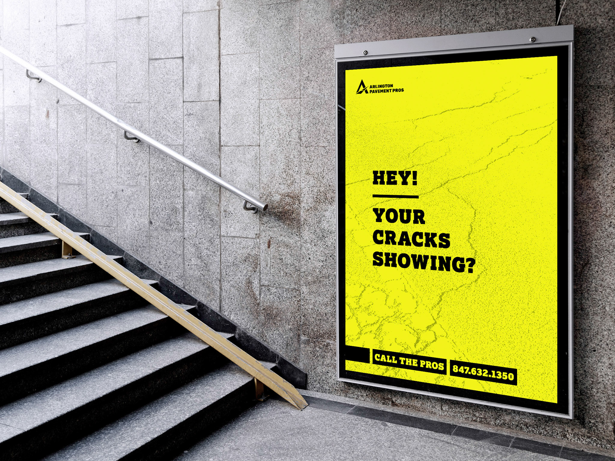 """This is a mock up of APP's main brand messaging in a subway. Solid black letterforms on bright yellow with a faint image of a cracked parking lot. The ad reads: """"Hey! Your crack's showing? Call the pros."""""""