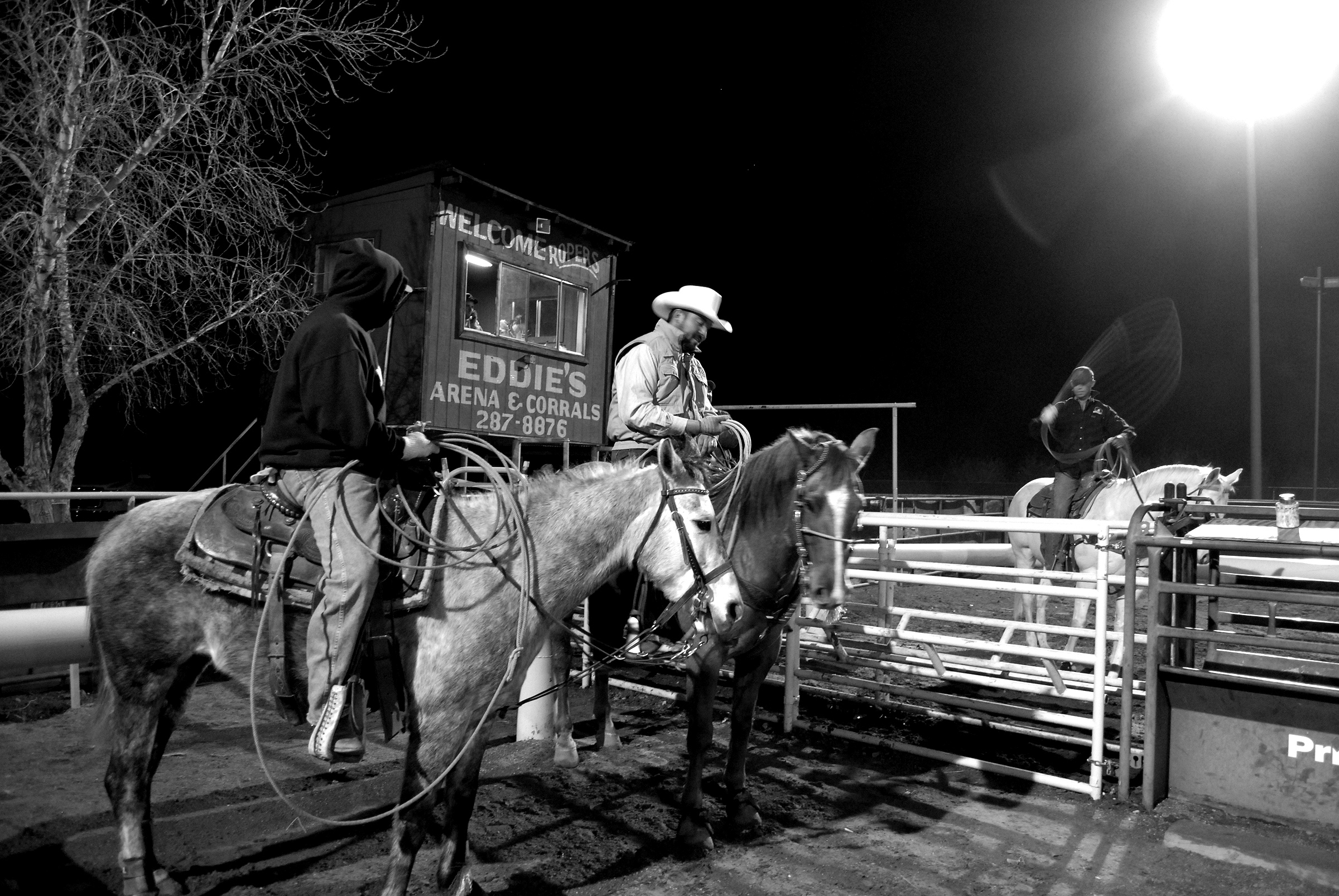Three cowboys on horseback holding lassos in a small rodeo arena