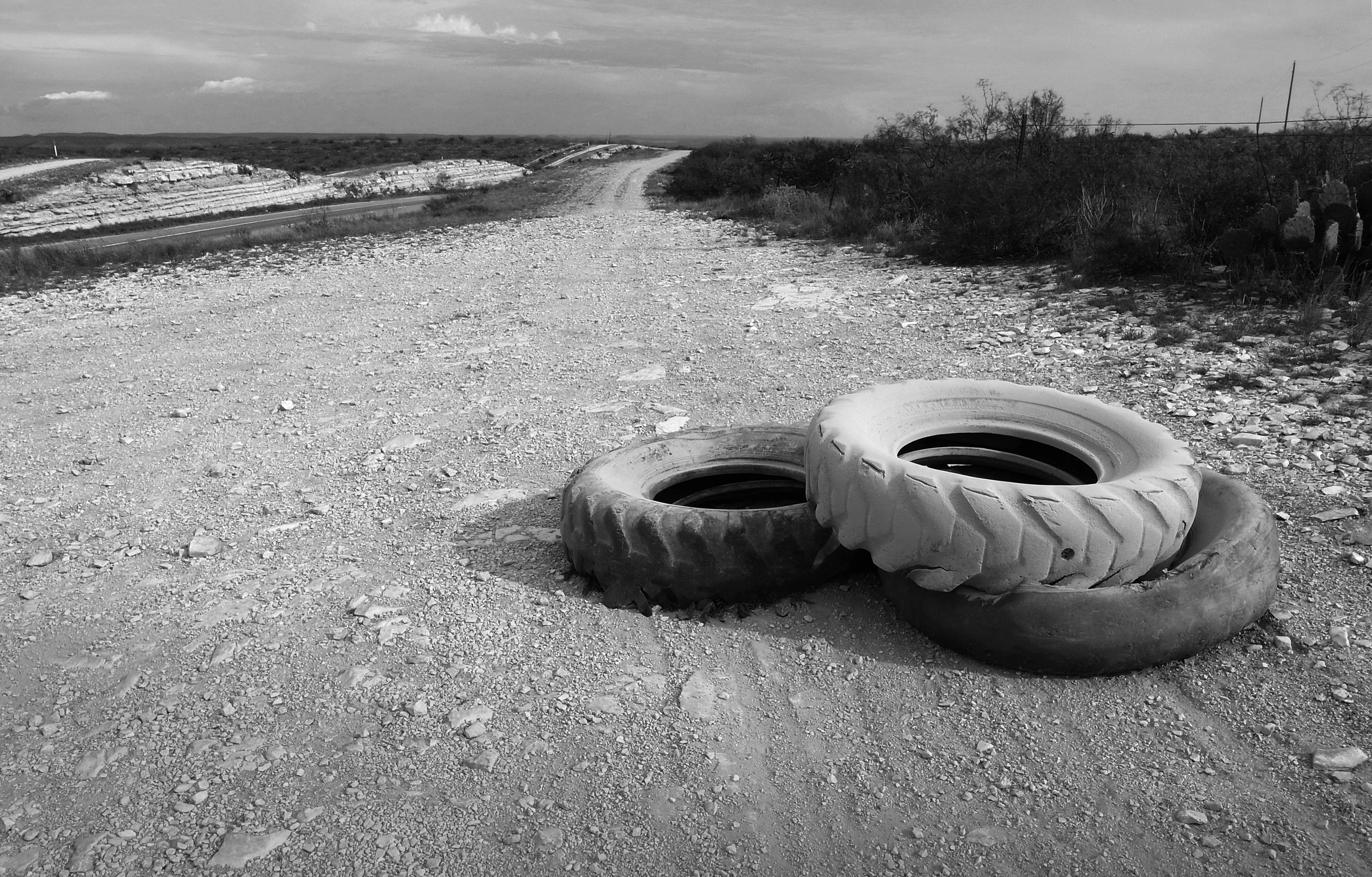 Three old truck tires that have been dragged across the dirt near a desert road