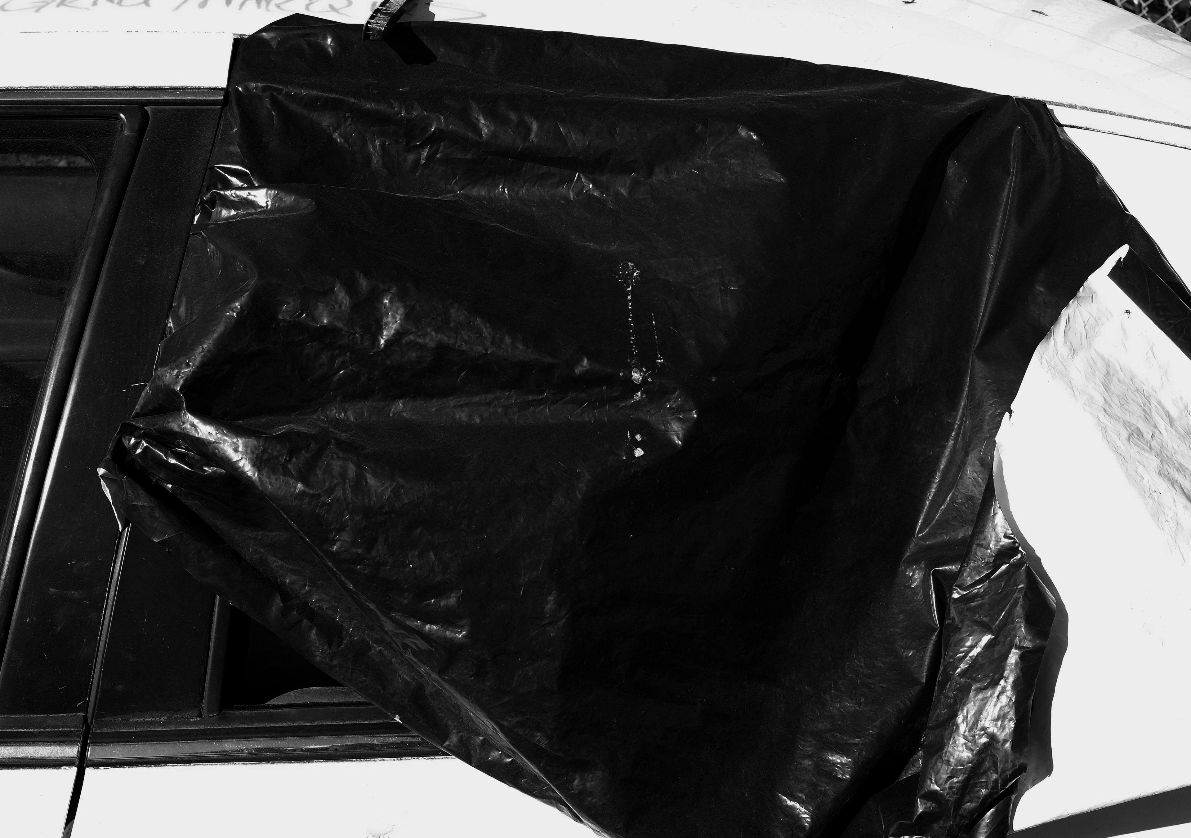 Black garbage bag covers a broken car window