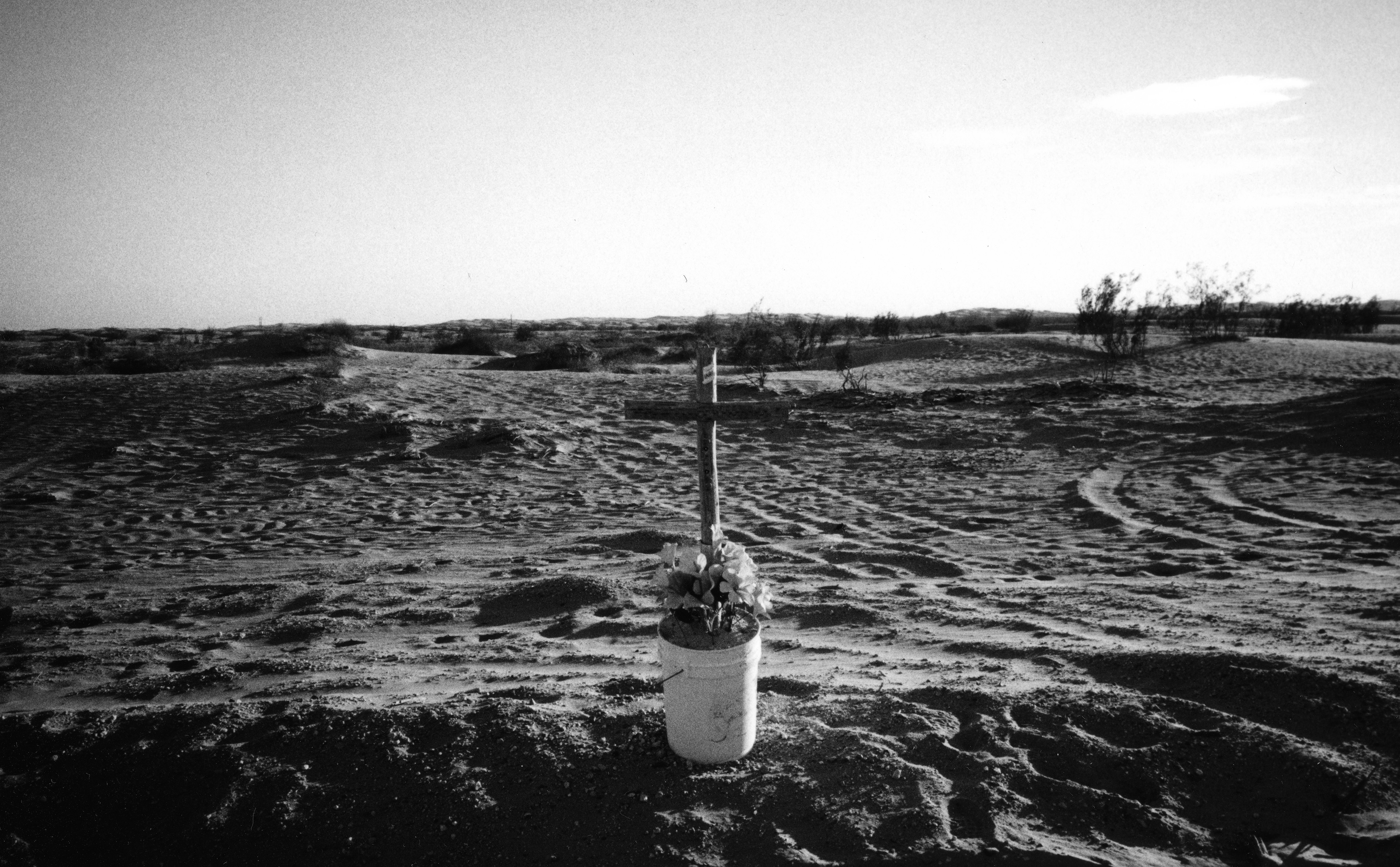 A wooden cross in a bucket with flowers in a desert landscape
