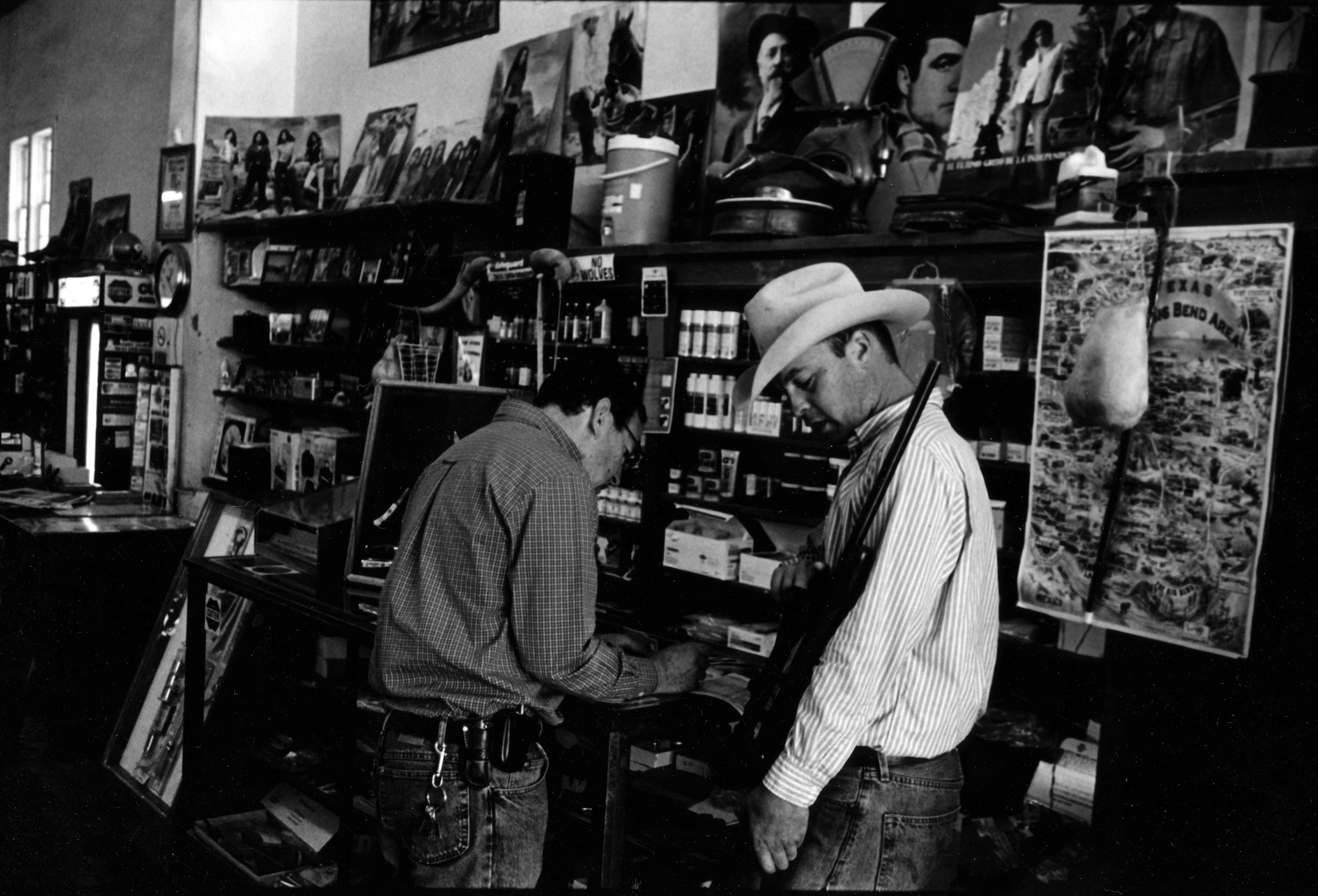 A young man in a cowboy hat holds a rifle while a sales person helps him in a store