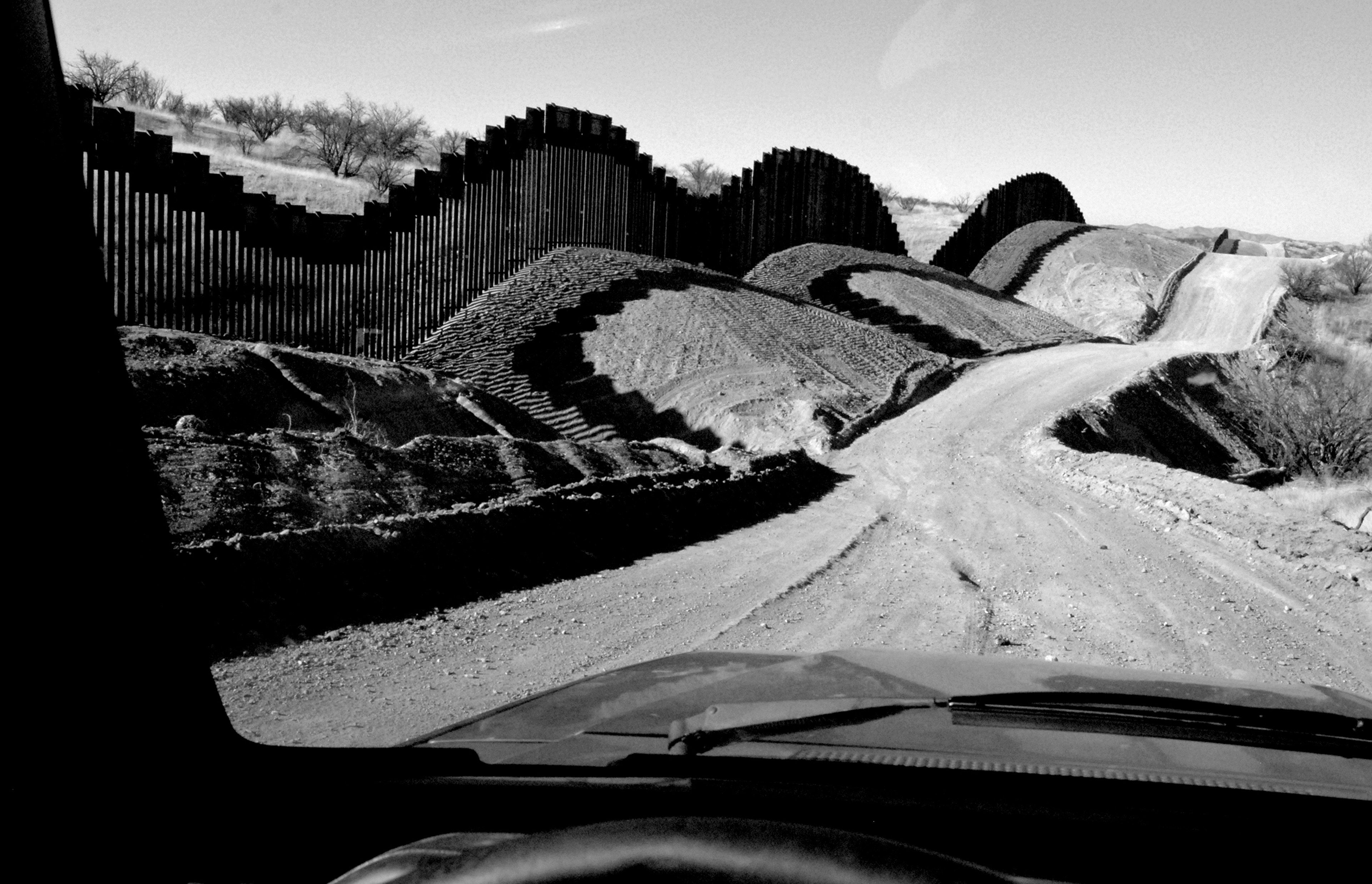 A dirt road with an undulating fence seen from the windshield of a car