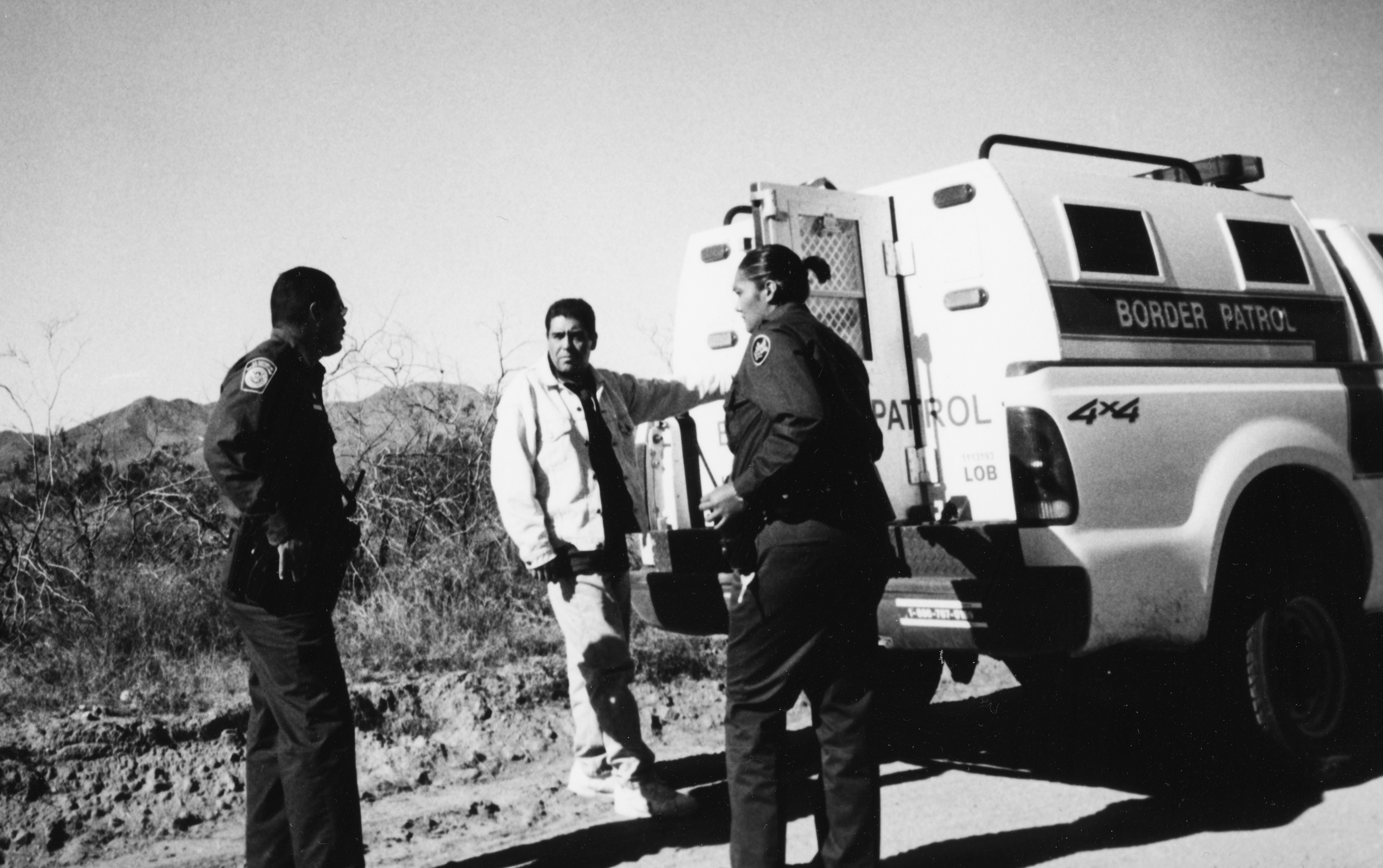 Boder patrol agents and a man behind a border patrol truck