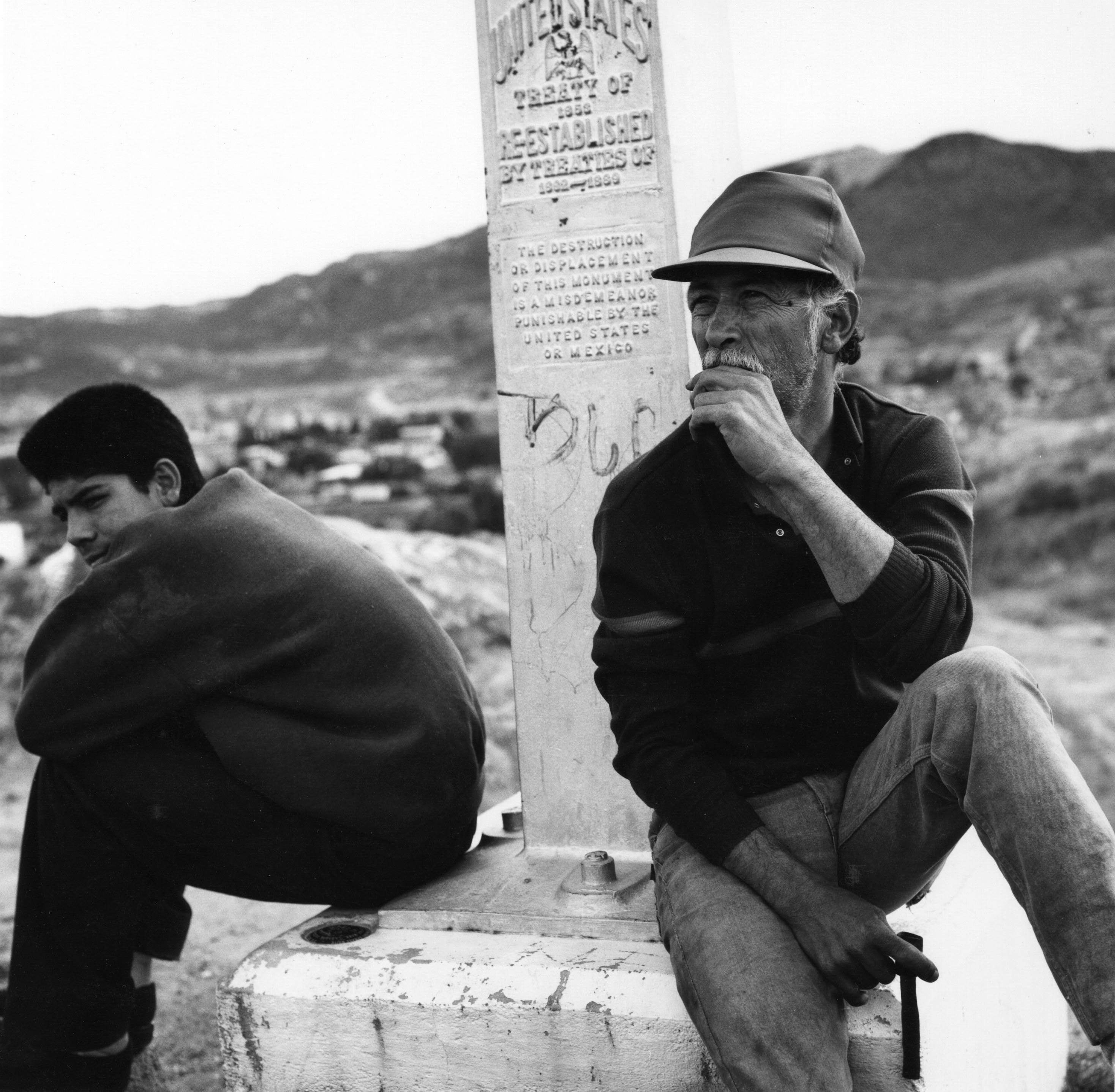 A young man and an old man sit on a US Mexico boundary monument