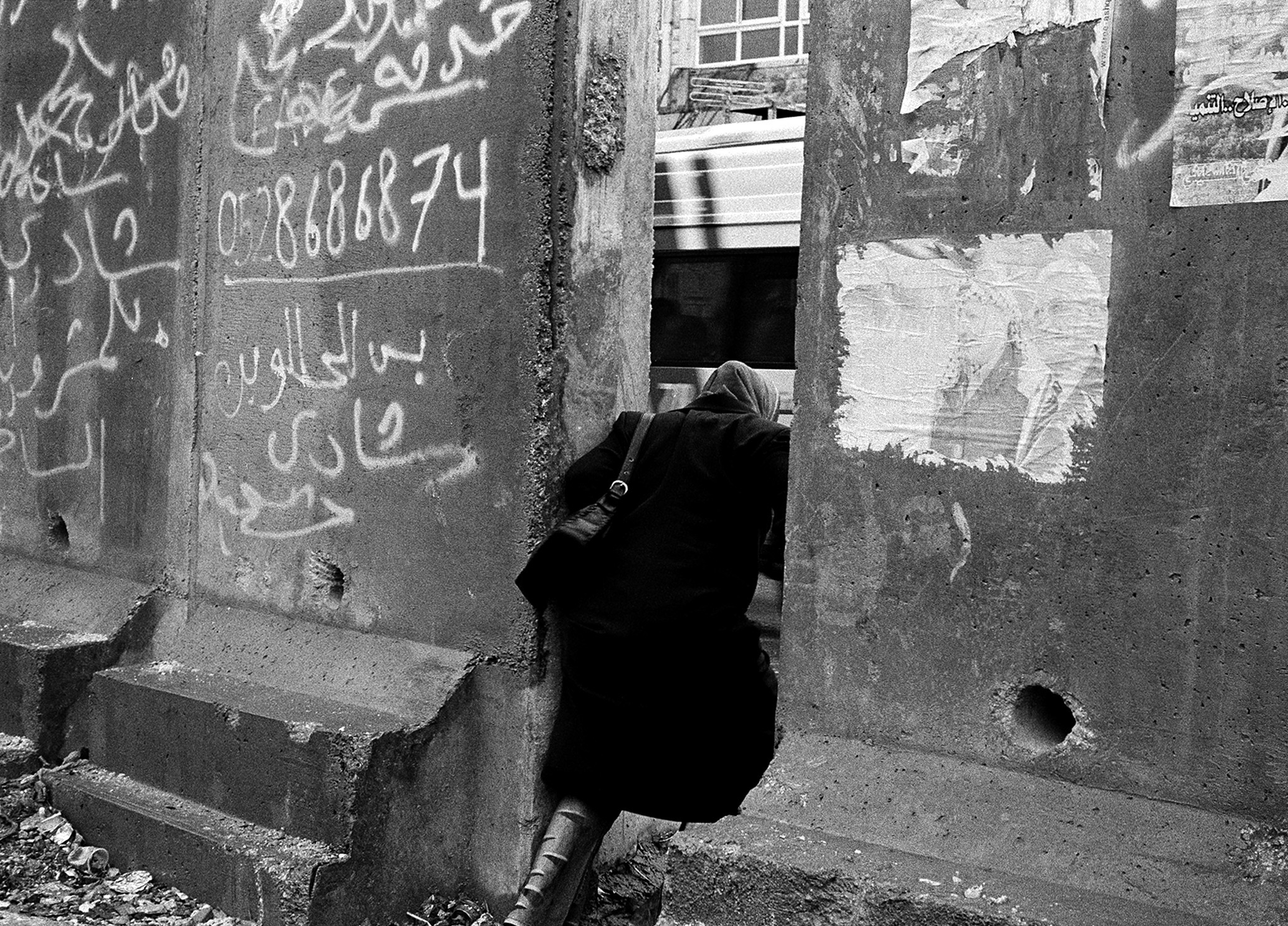 A woman wearing a head scarf and long black dress crosses at a gap in a concrete wall