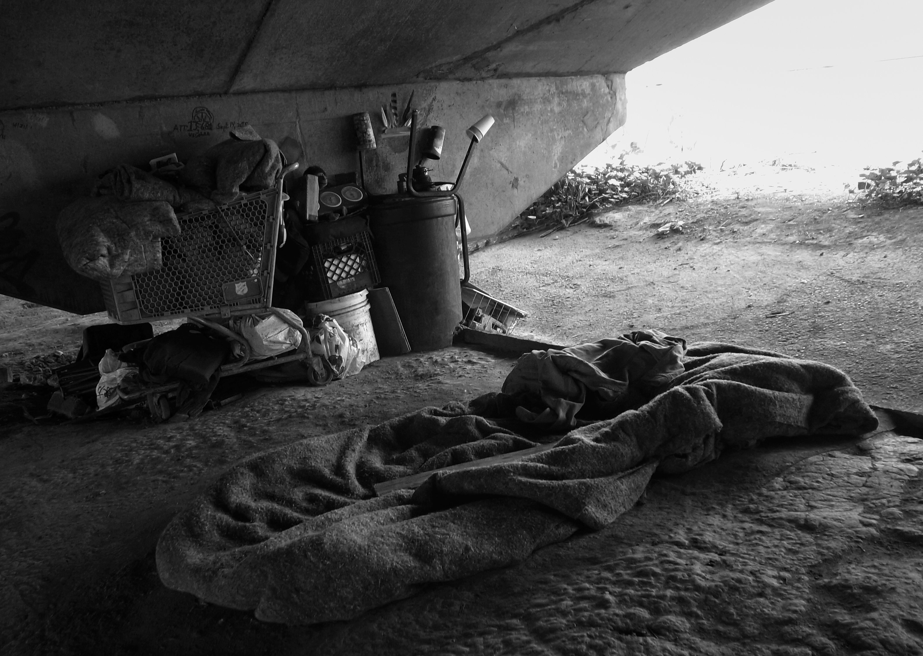 A shopping cart and objects next to a bed made of felt blankets under an overpass