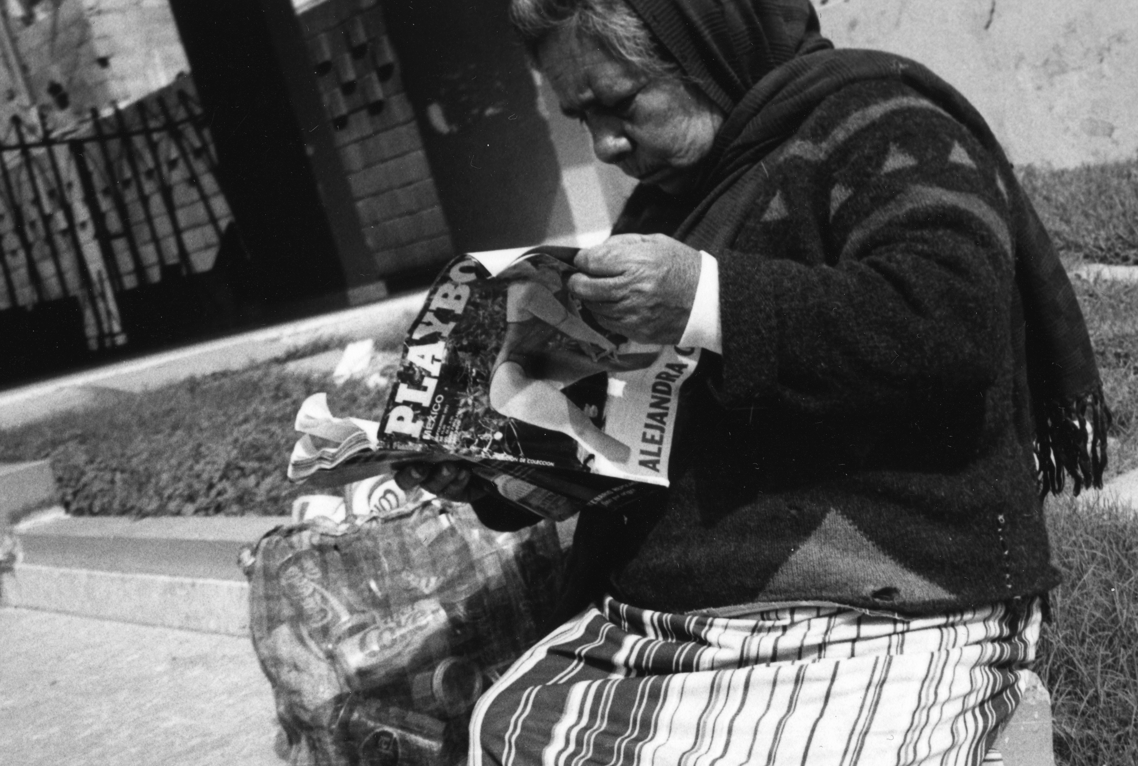 An old woman sitting with a bag full of soda cans reads a Playboy magazine