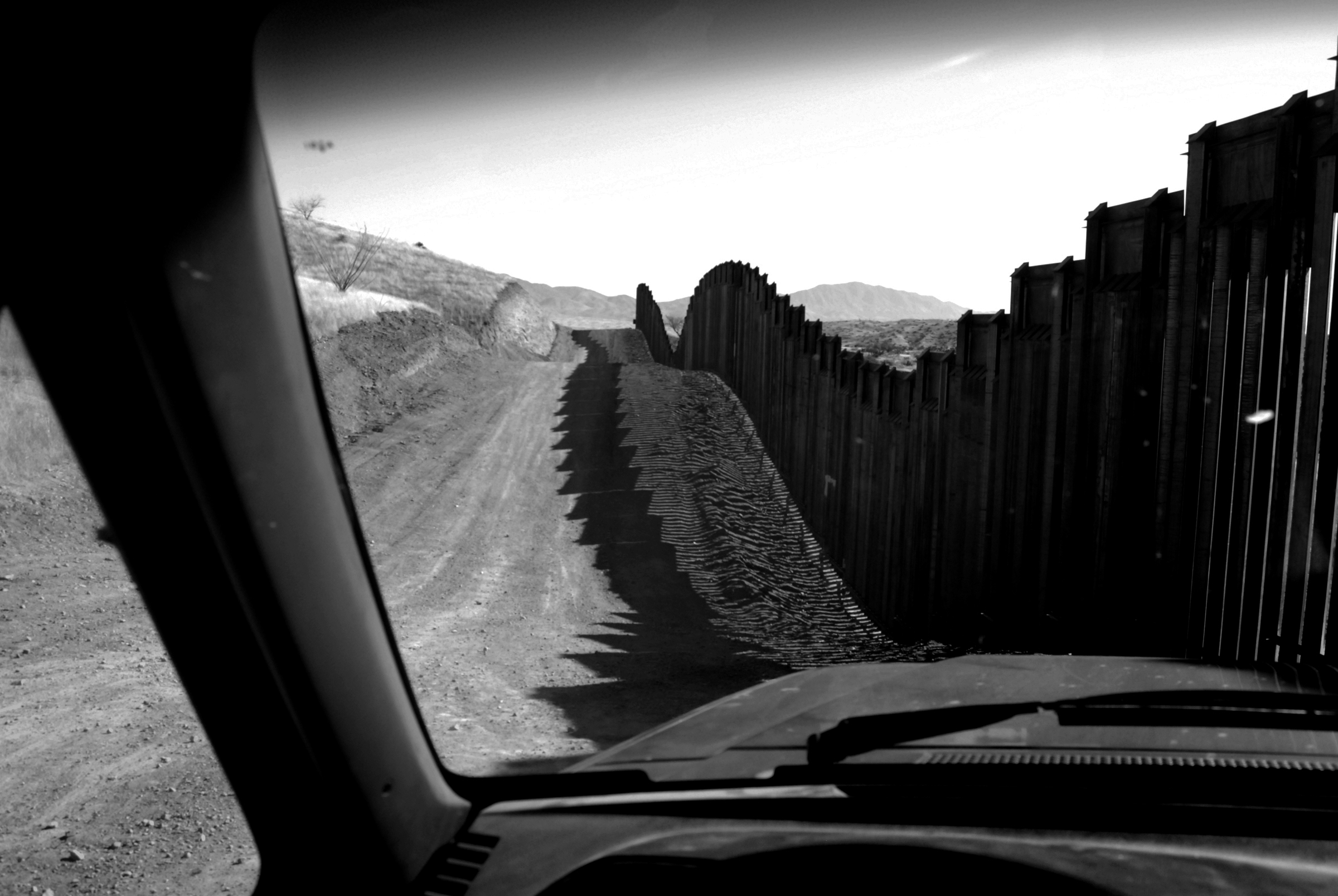 View of a dirt road and a black, undulating fence from a car