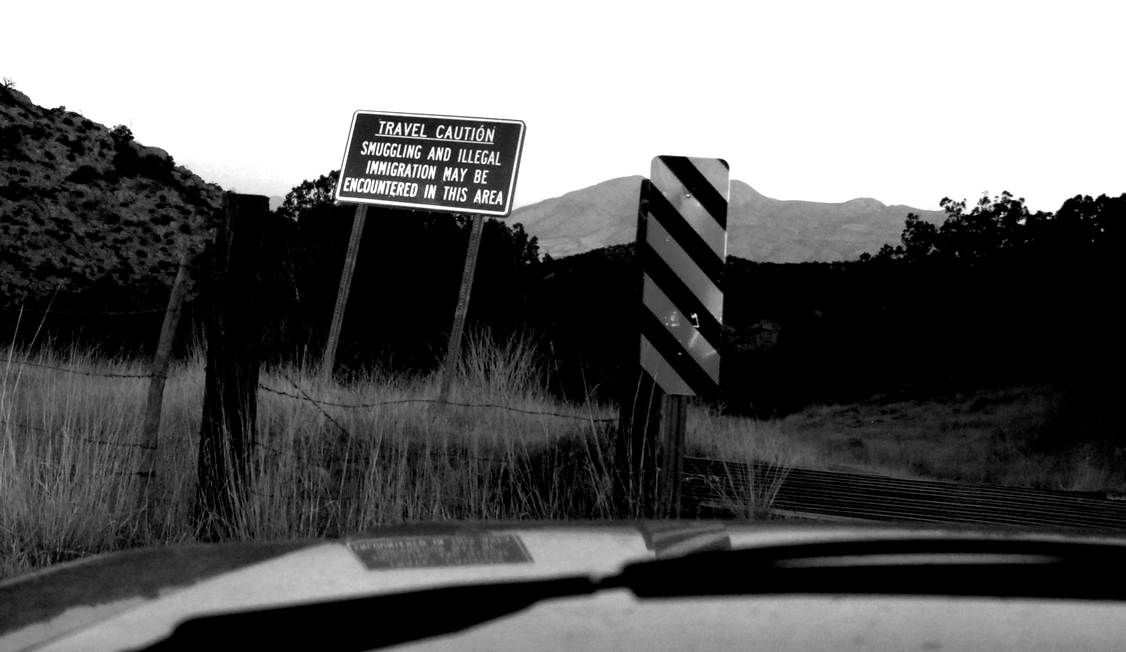 "View of a road sign from a car reads ""Travel Caution: smuggling and illegal immigration may be encountered in this area"""