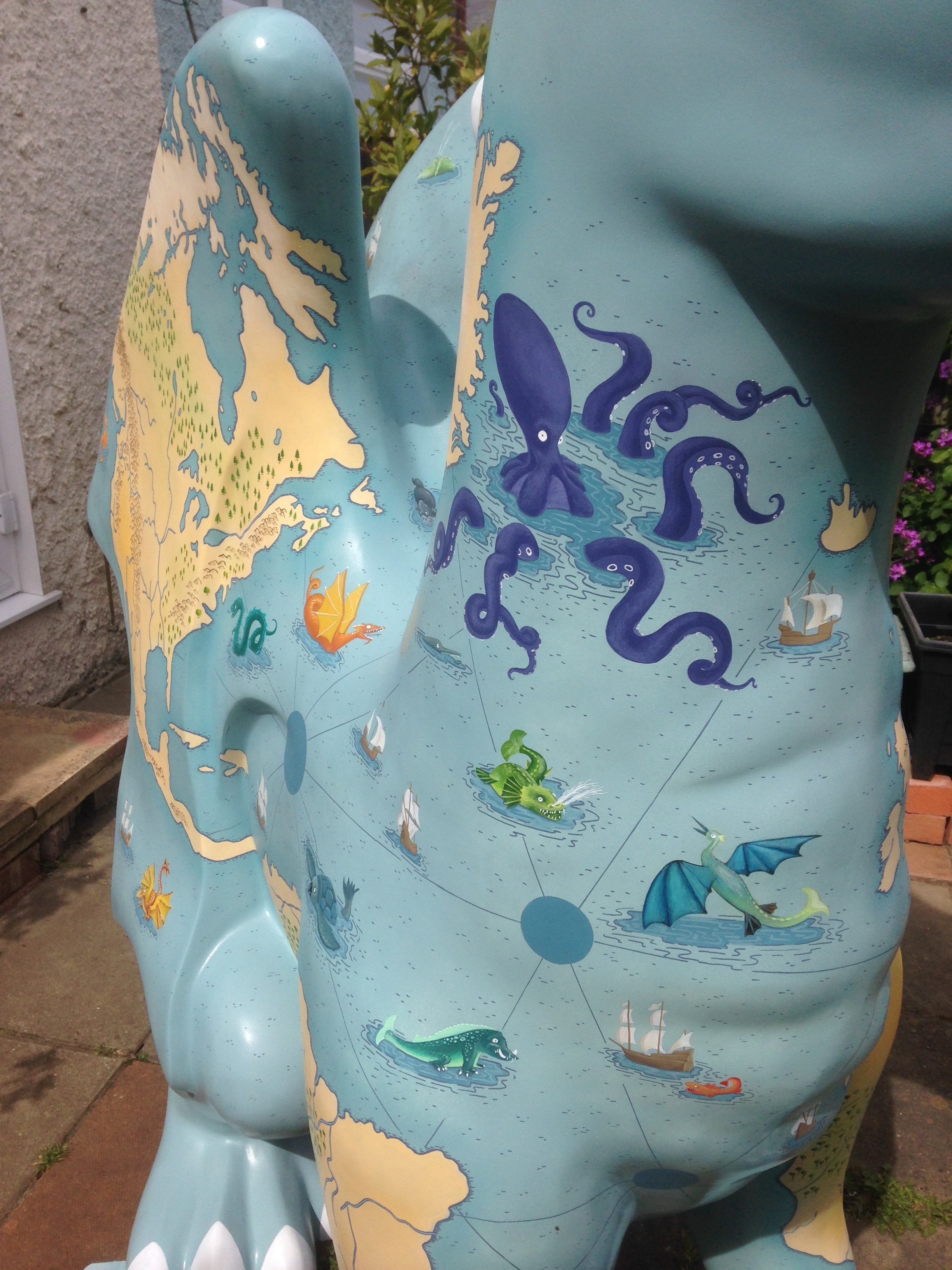 Close up of pained sea monsters on a Dragon sculpture painted with an illustrated map of the world. By Fiona Gowen. Part of the GoGoDragons! Trail in Norwich in 2015