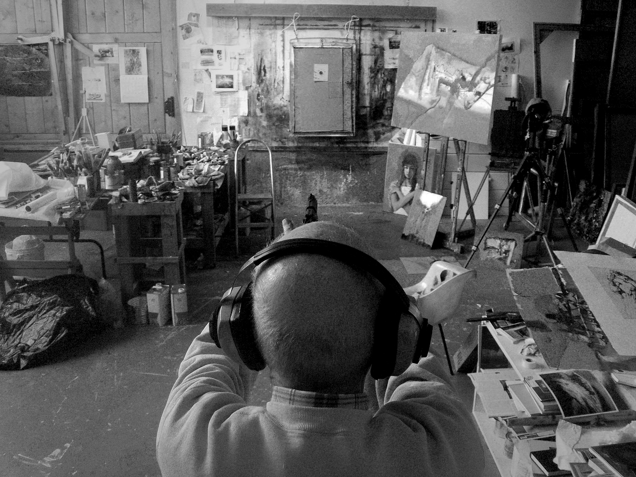 A man seen from the back shoots a target inside a painting studio