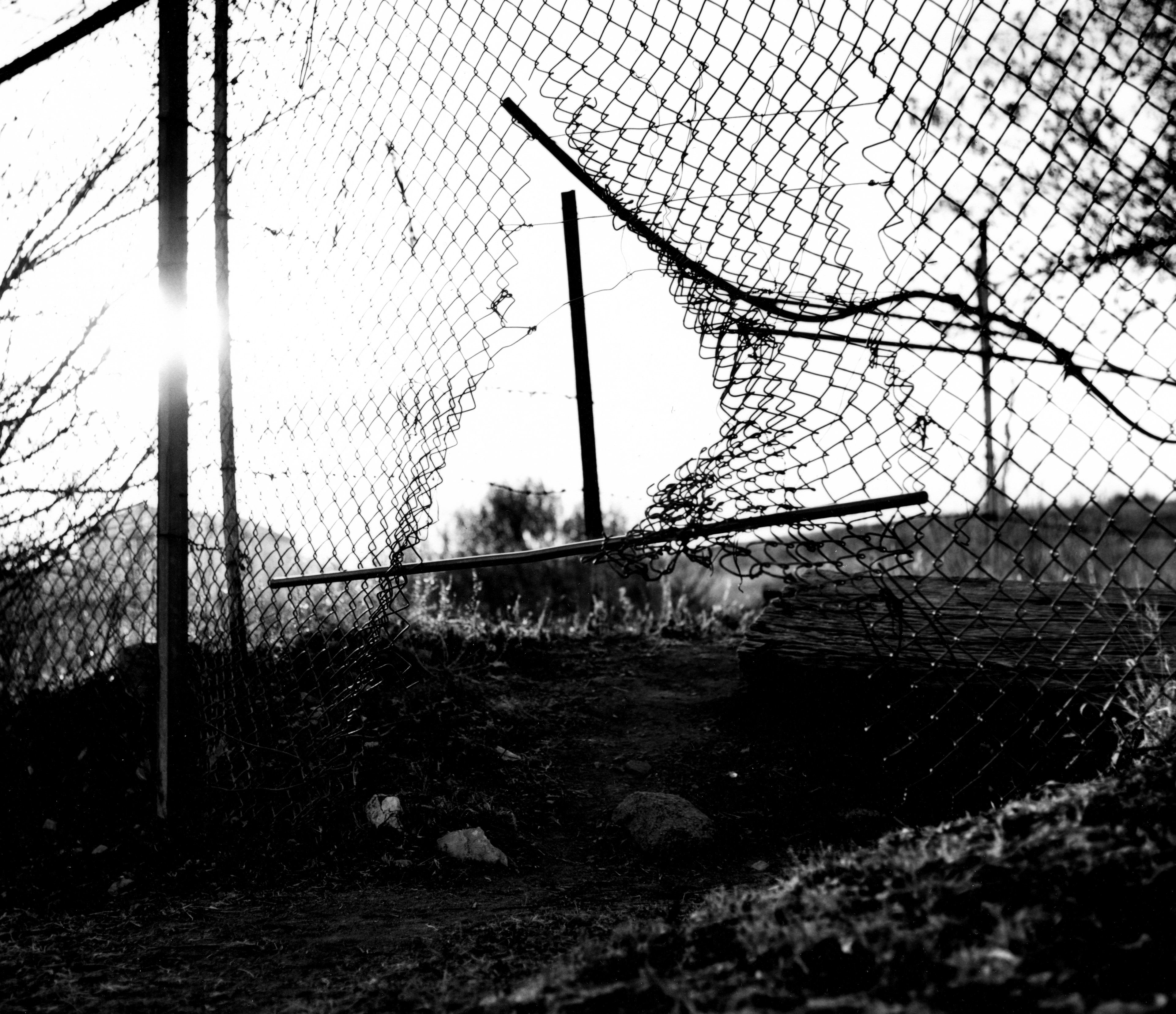 A chain link fence with a hole in a landscape