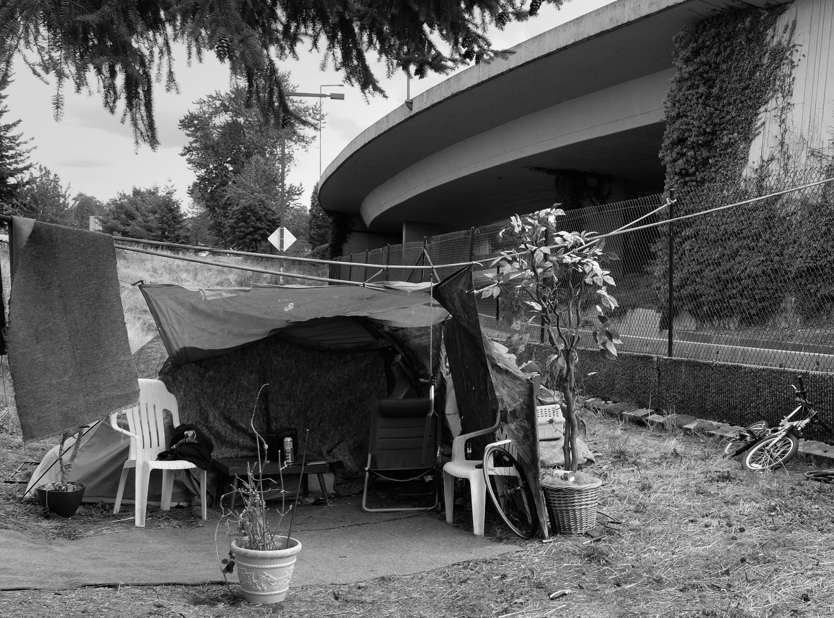 Plastic chairs, potted plants and a tarp in a wooded area near a turn off and overpass