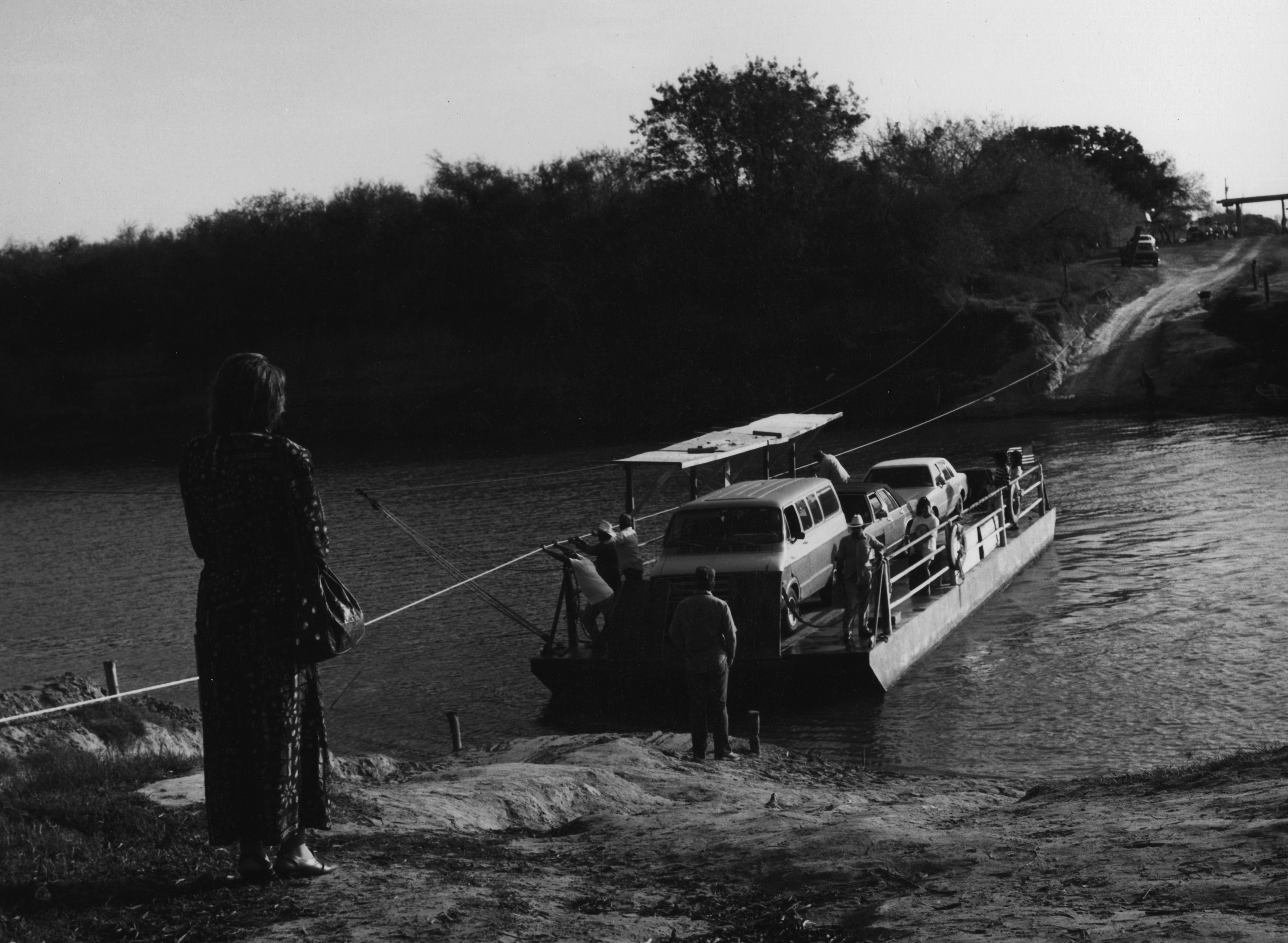A woman seen from behind watches a group of men in a hand operated ferry cross a river