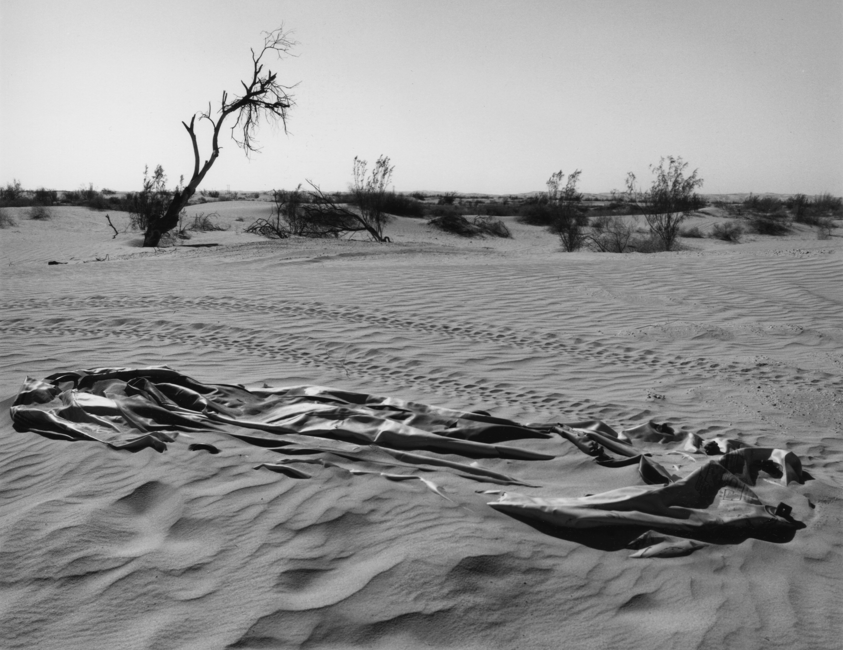 A deflated rubber raft is partly buried in the sand in a desert landscape